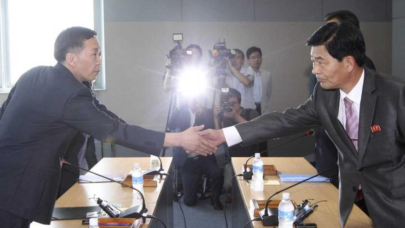 El representante de Corea del Sur, Kim Ki-woong, y el de Corea del Norte, Park Chol-su, cierran con un apretón de manos el acuerdo para reabrir Kaesong.