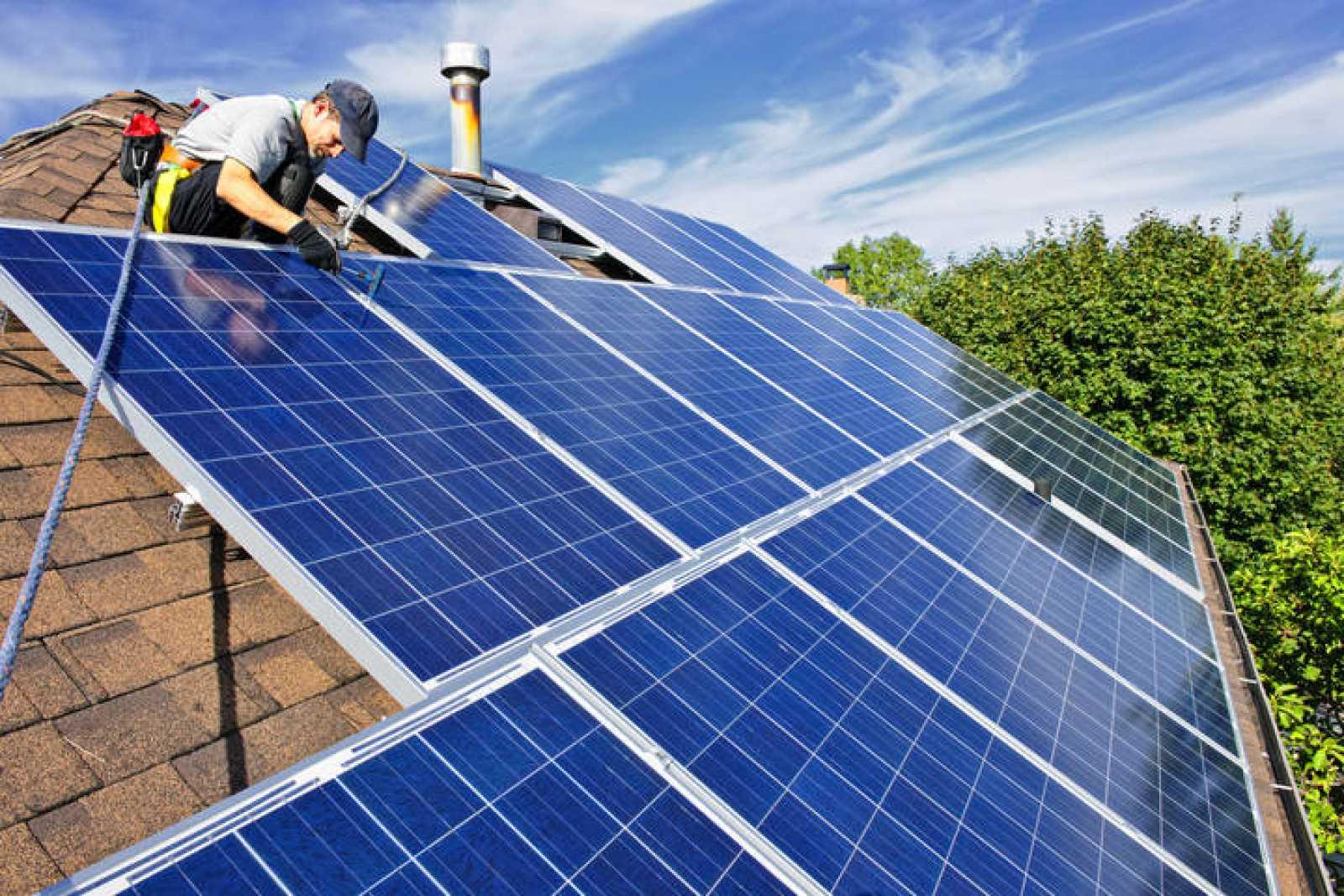 Un operario instala paneles solares en el tejado de una casa