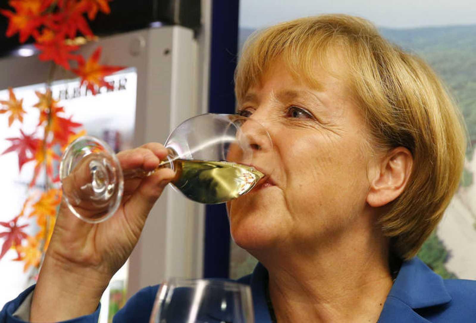 La canciller alemana Angela Merkel bebe vino para celebrar su victoria en las elecciones generales