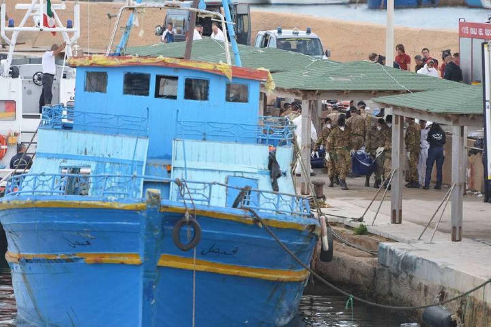 Soldados italianos llevan el cuerpo de uno de los inmigrantes muertos en Lampedusa, Italia