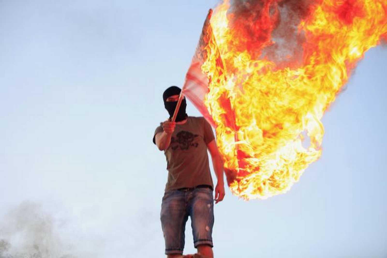 Un libio protesta quemando una bandera en Bengasi.