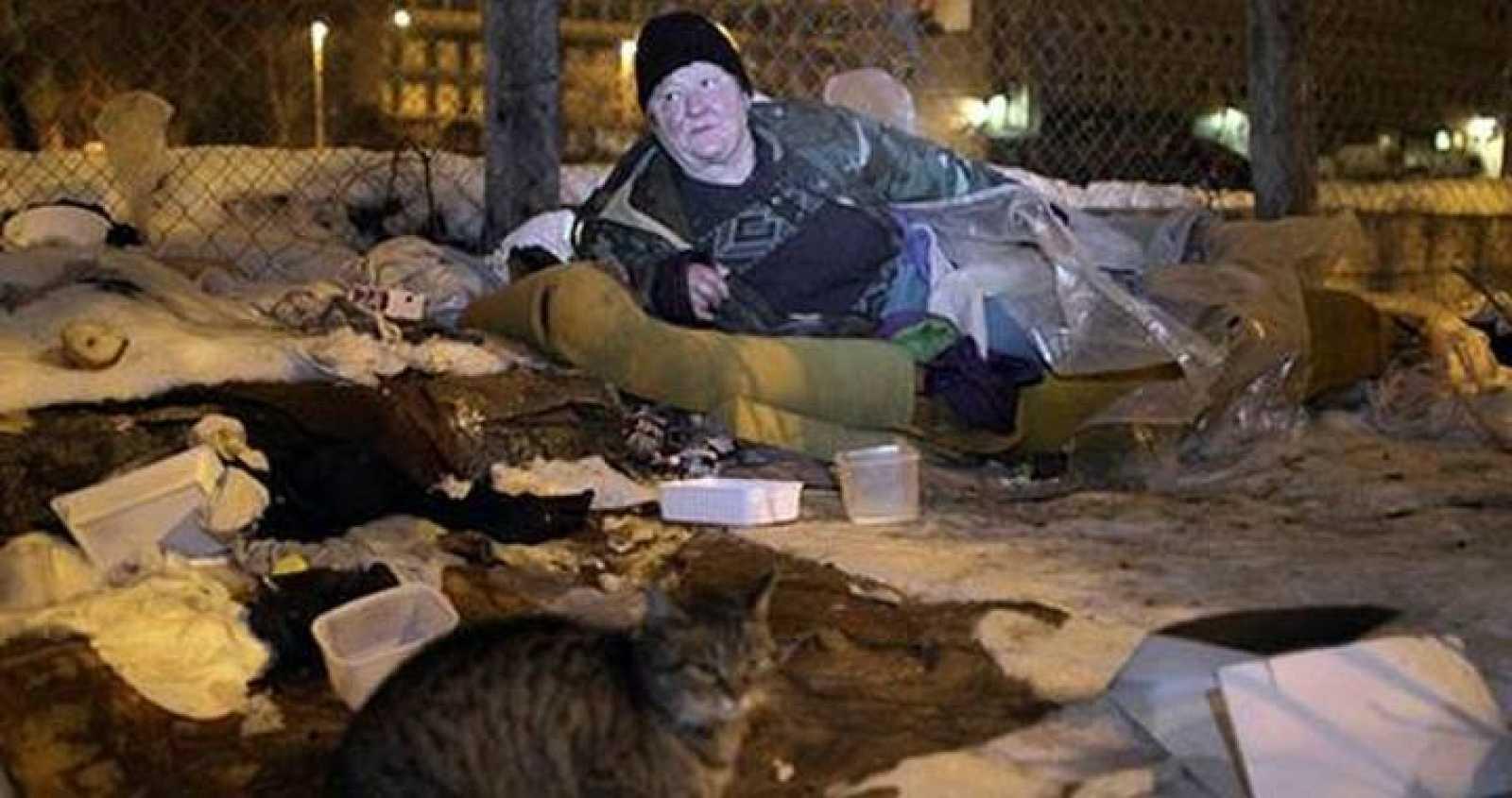 Una mujer sin hogar descansa en un saco de dormir en un parque público en Budapest.