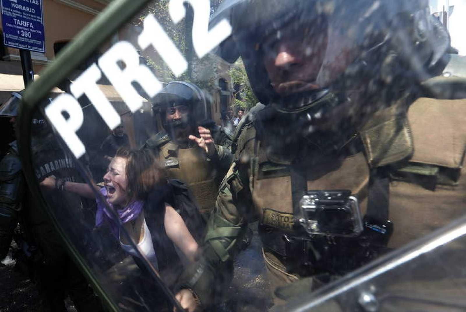 Una manifestante es detenida por miembros de la Policía de Carabineros en Santiago de Chile