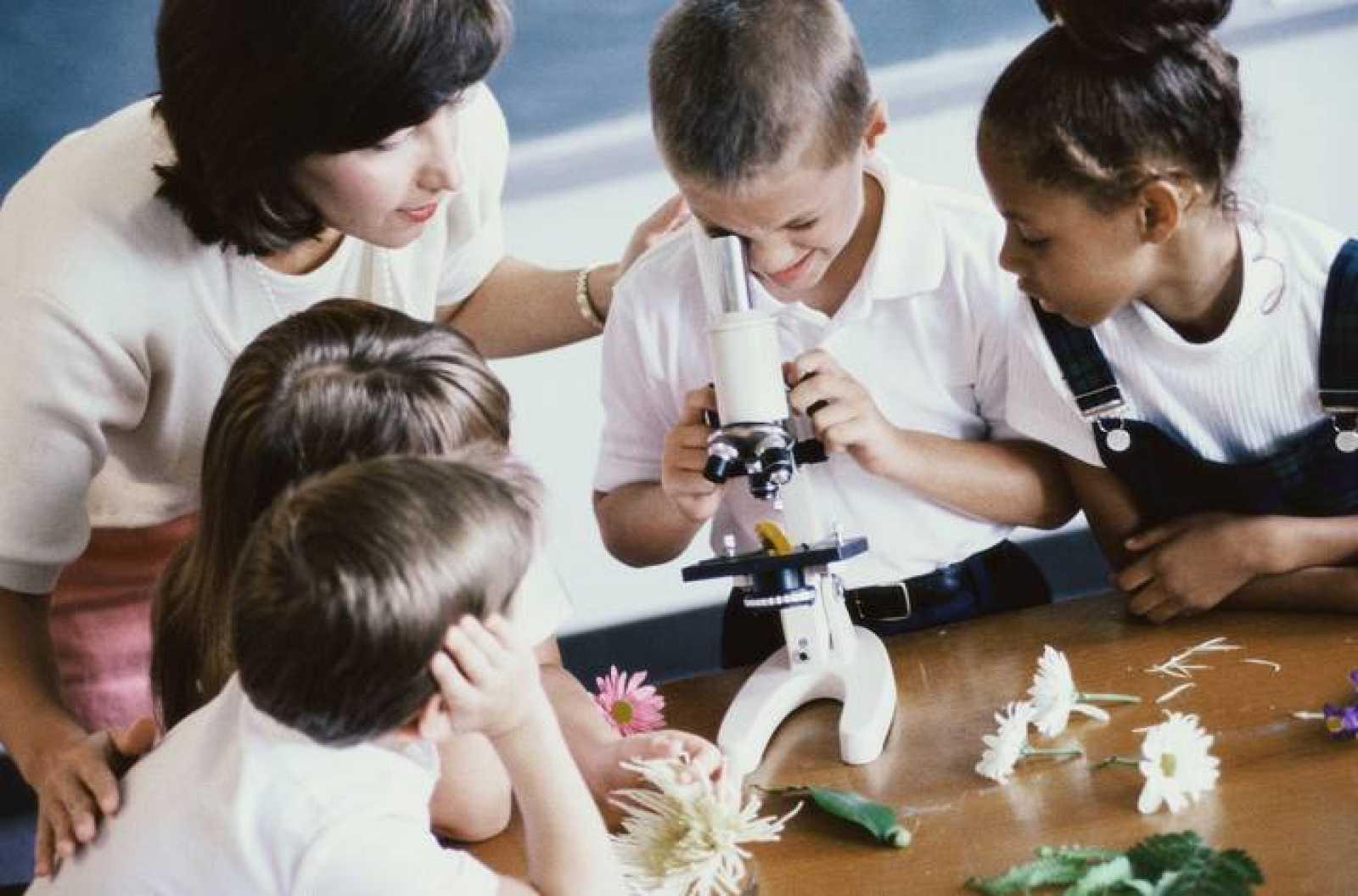 Niños mirando con un microscopio.
