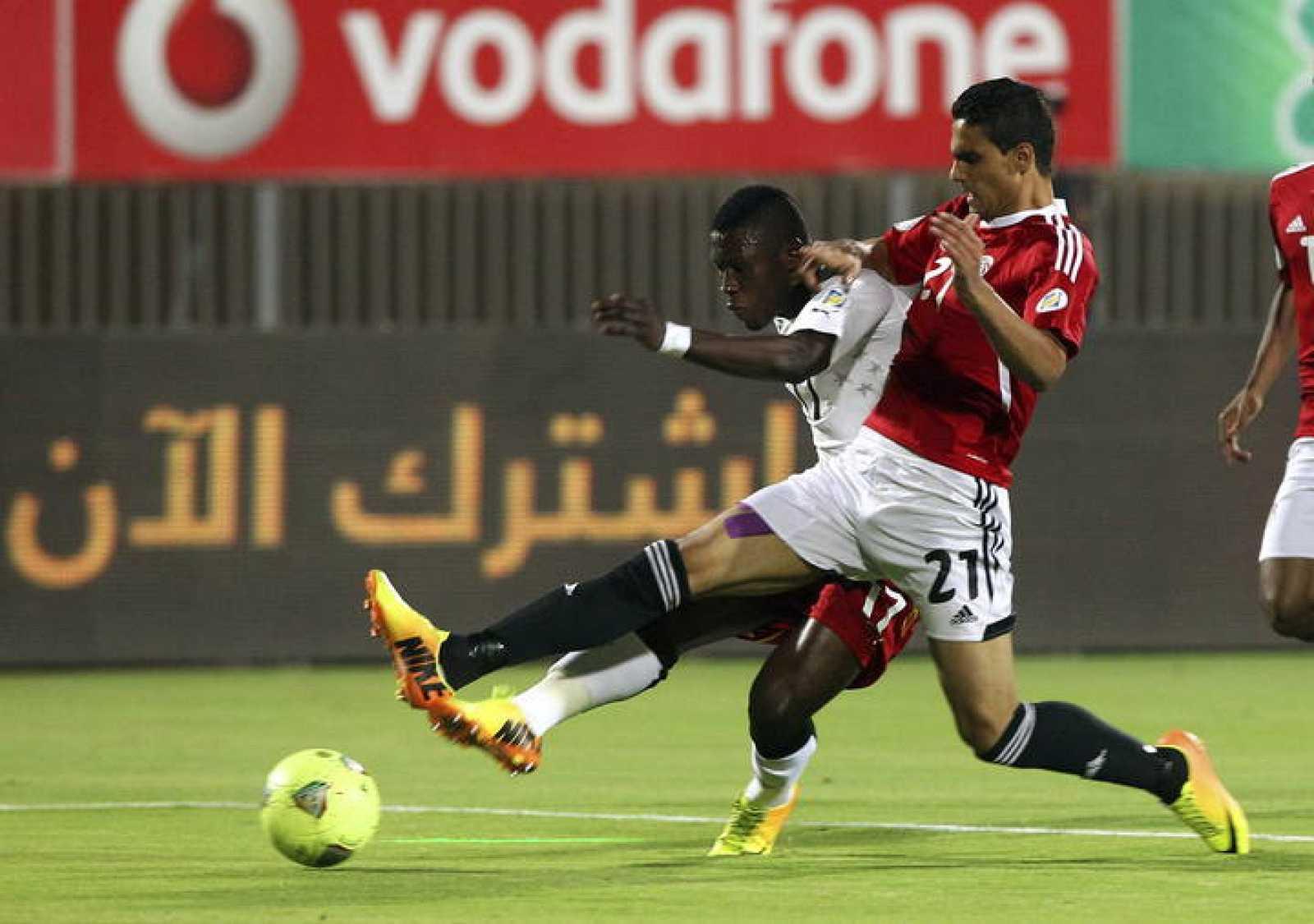 El futbolista egipcio Mohamed Nagieb (d) pelea por el control del balón frente al jugador ghanés Rashid Sumaila (i)