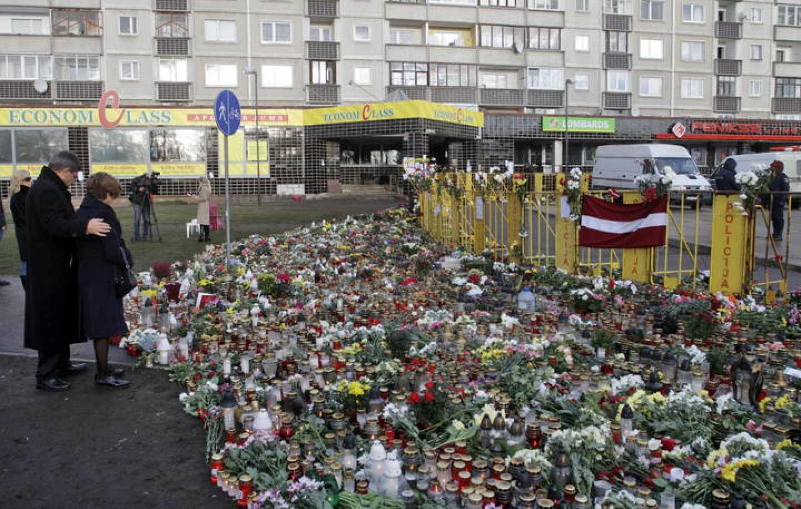 """El embajador polaco en letóonia Jerzy Marek Nowakowski y su mujer guardan un minuto de silencio en recuerdo de las víctimas del derrumbe del edificio comercial """"Máxima"""", en el centro de Riga, Letonia, el 25 de noviembre del 2013"""