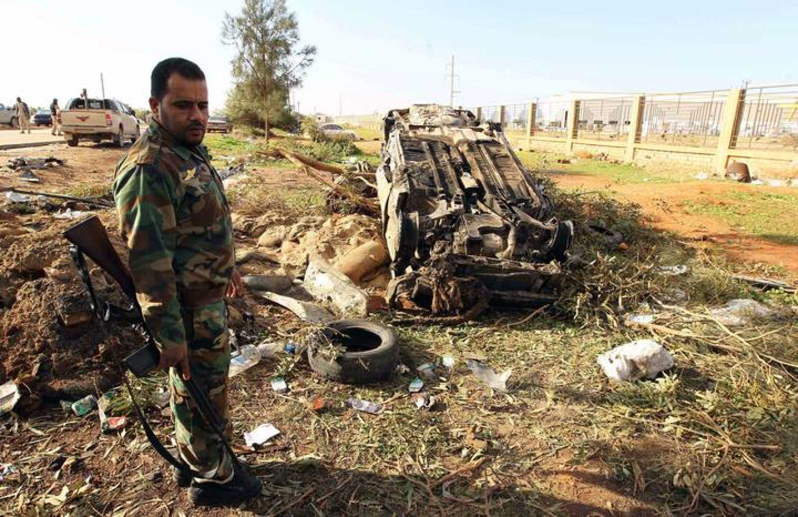 Un miembro de las fuerzas de seguridad de Libia, junto a uno de los vehiculos destruidos en el ataque con coche-bomba en Bengasi