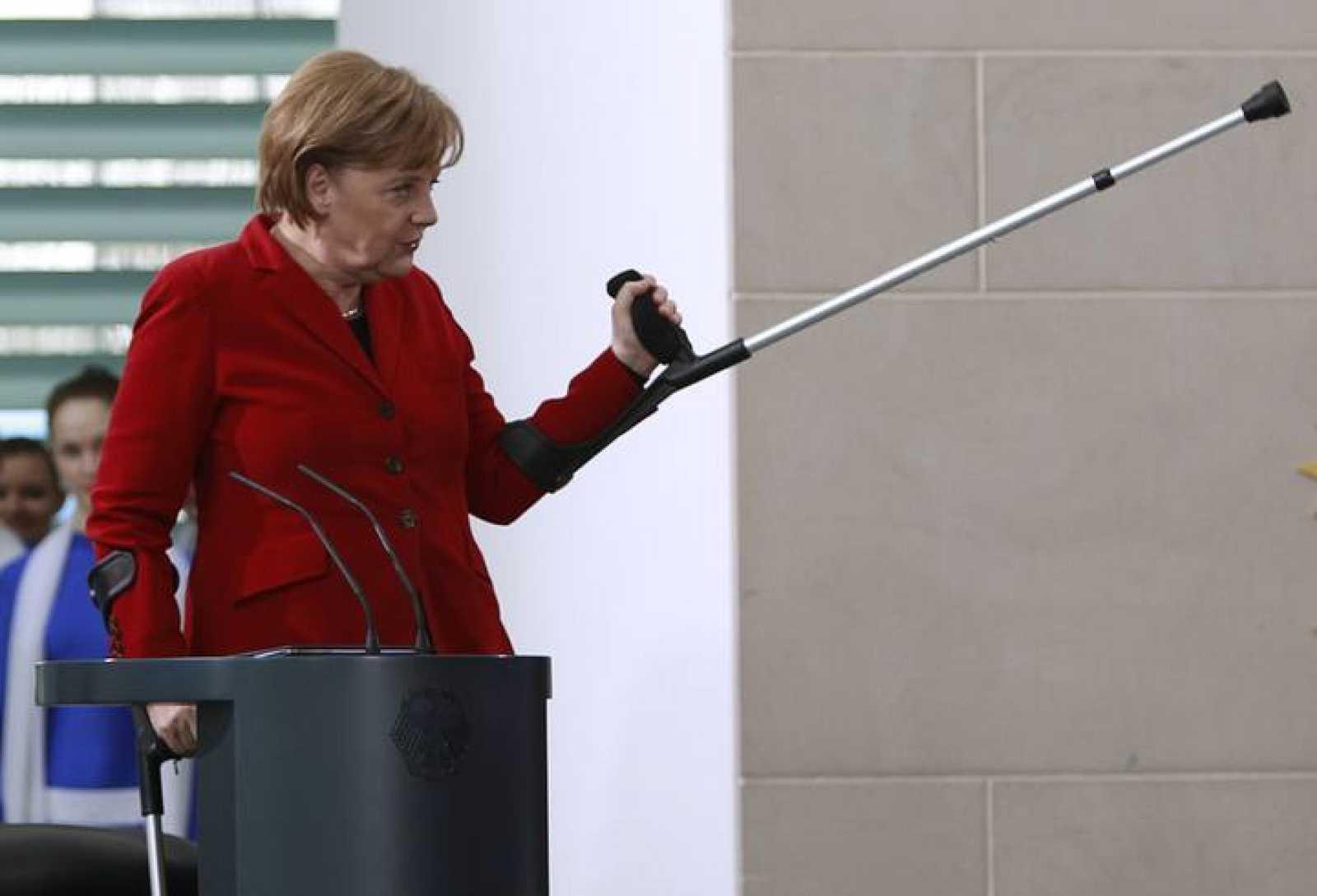 Angela Merkel hace un gesto con una muleta, tras fracturarse la pelvis