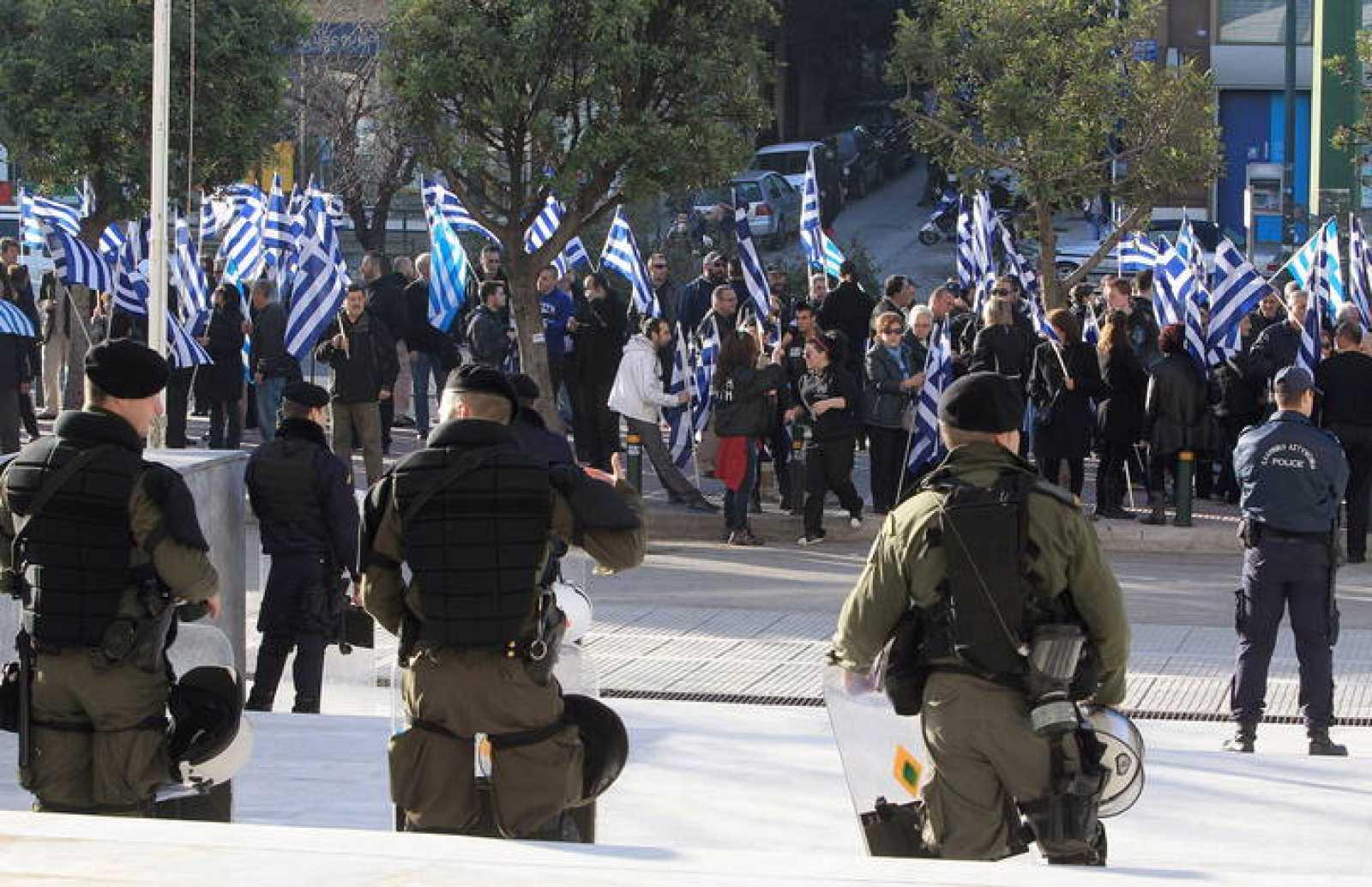 Policías y militares griegos vigilan a unos manifestantes en Atenas