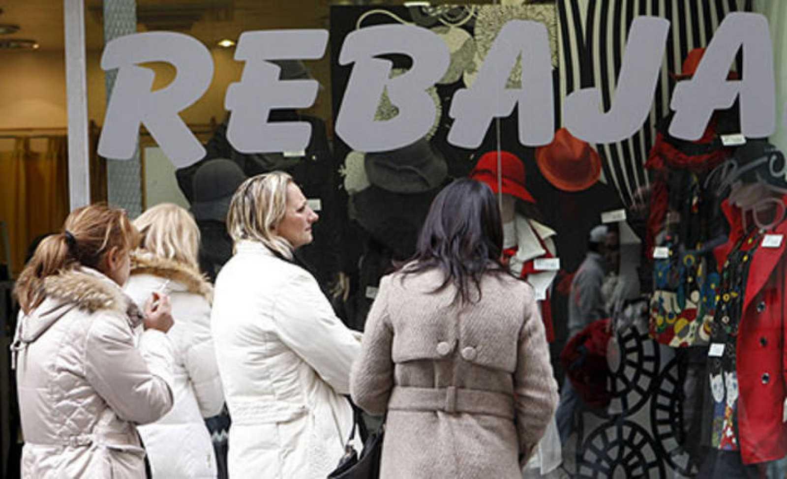 Varias mujeres contemplan un escaparate en rebajas