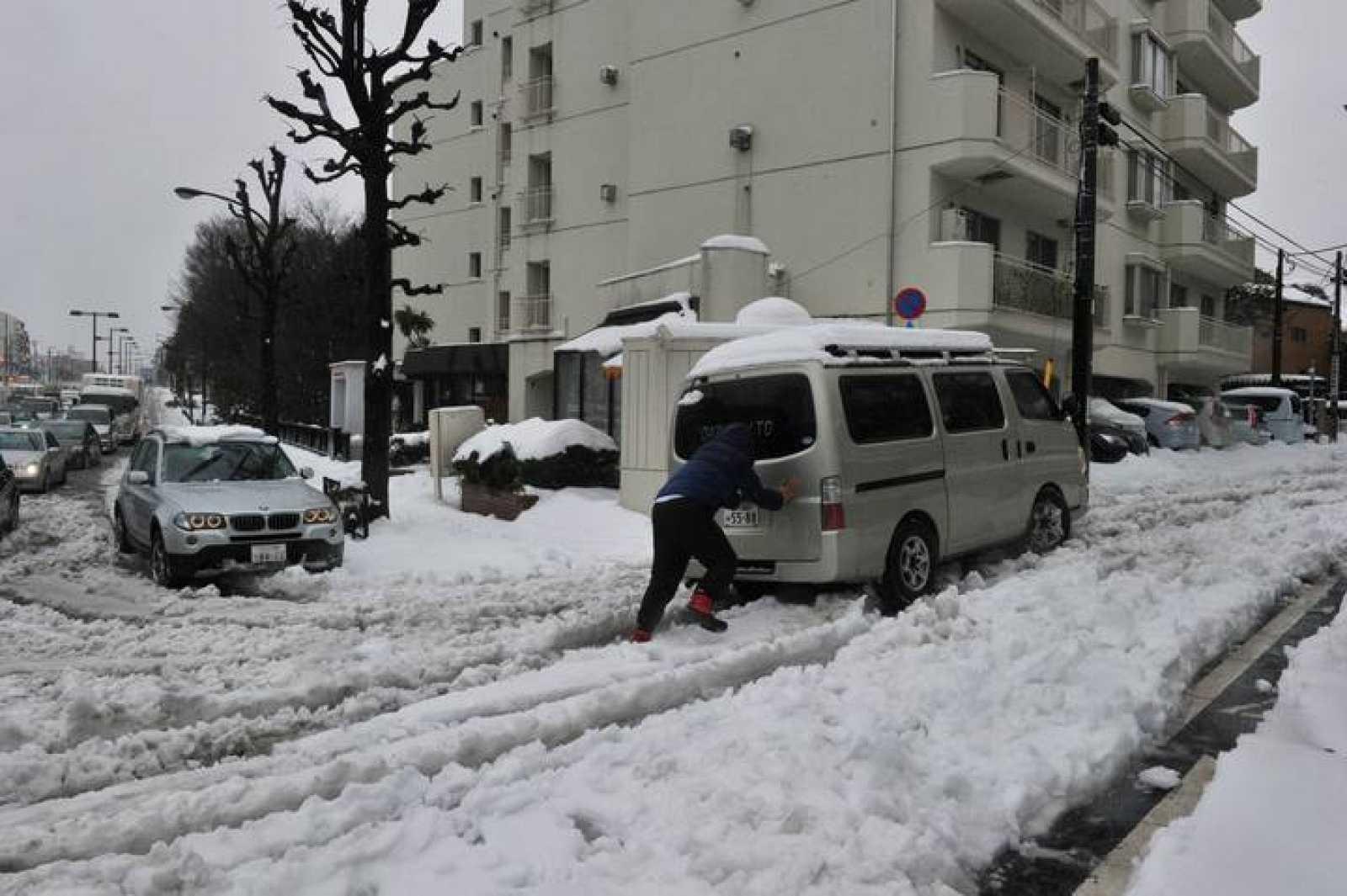 Un hombre empuja su vehículo en una carretera nevada en Tokio