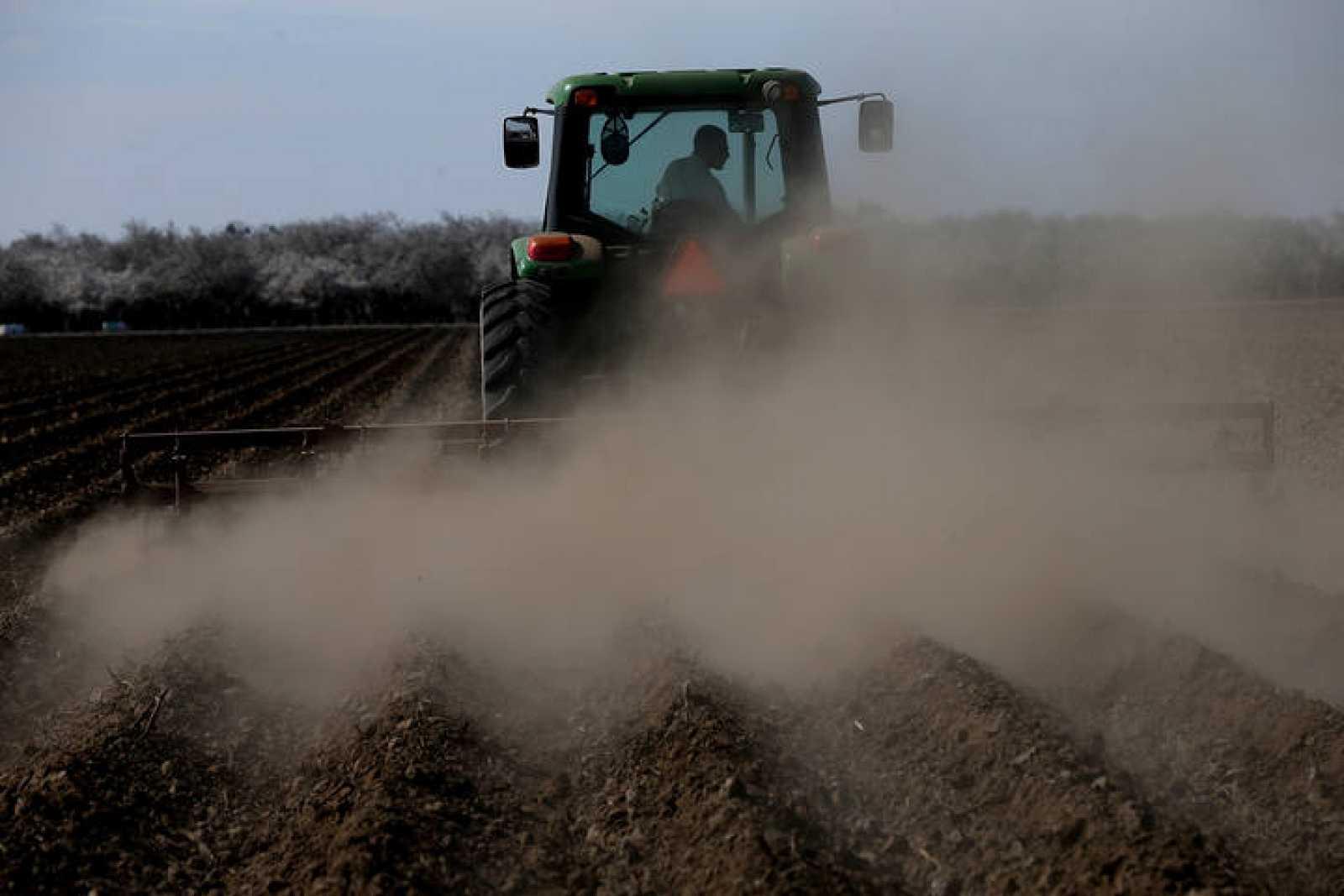 Un hombre ara el campo con su tractor