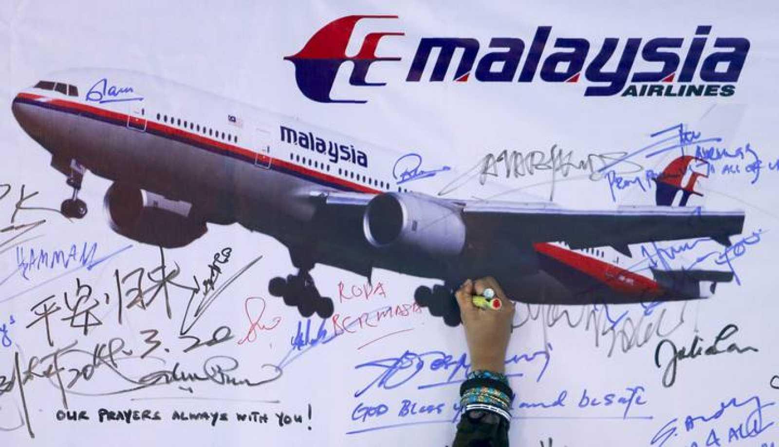 Un mujer escribe un mensaje en recuerdo del vuelo MH370 de Malaysia Airlines