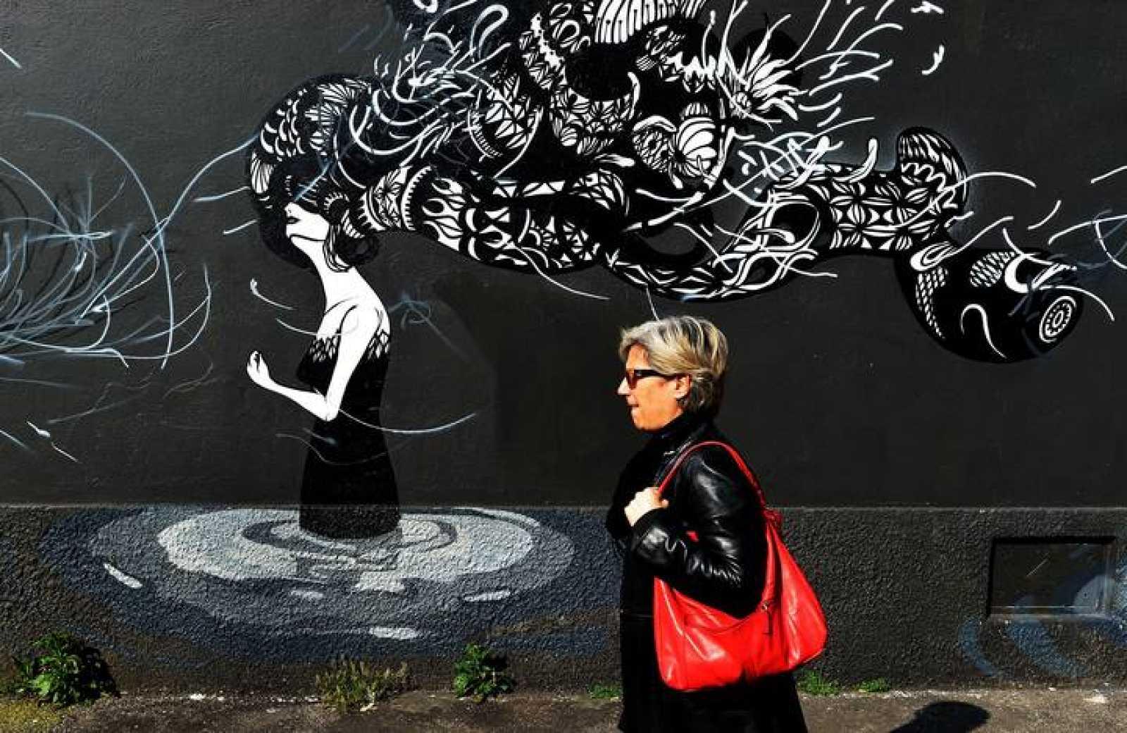 Una mujer pasa por delante de un graffiti