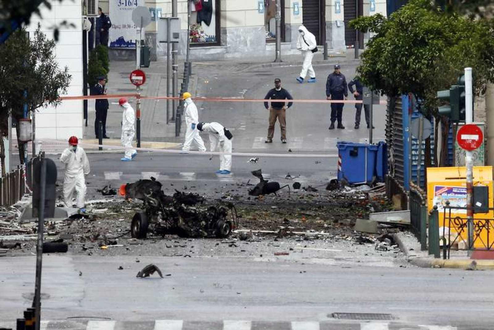 Expertos de la Policía buscan evidencias en el lugar de la explosión de un coche bomba, en Atenas