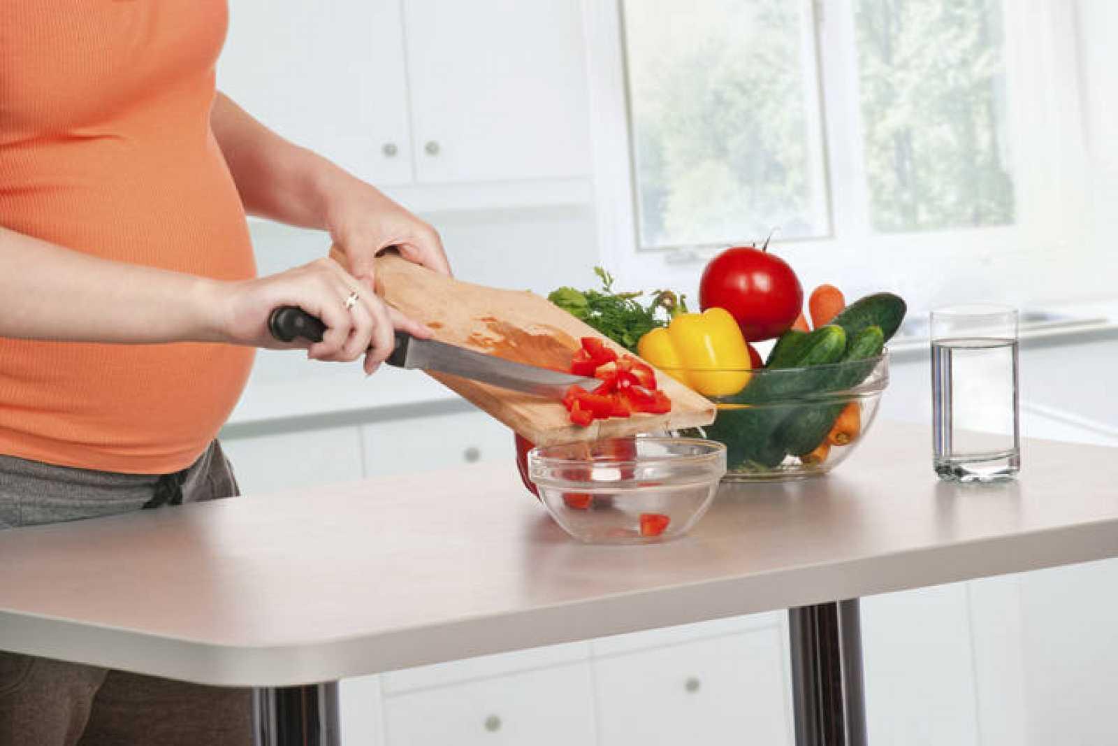 Mujer embarazada cocinando verduras.