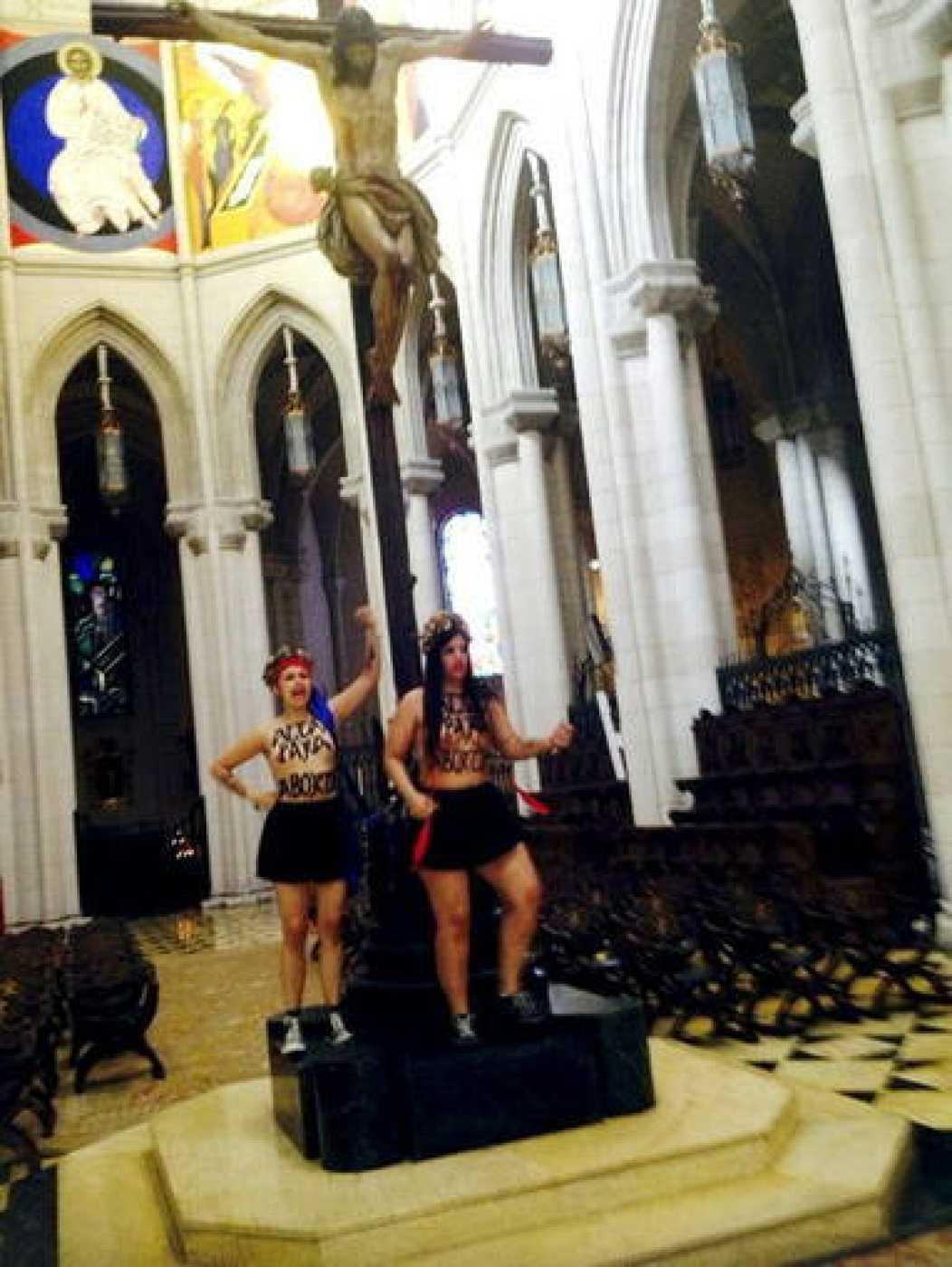 Las dos activistas de Femen encadenadas a un crucifijo en el altar de La Almudena