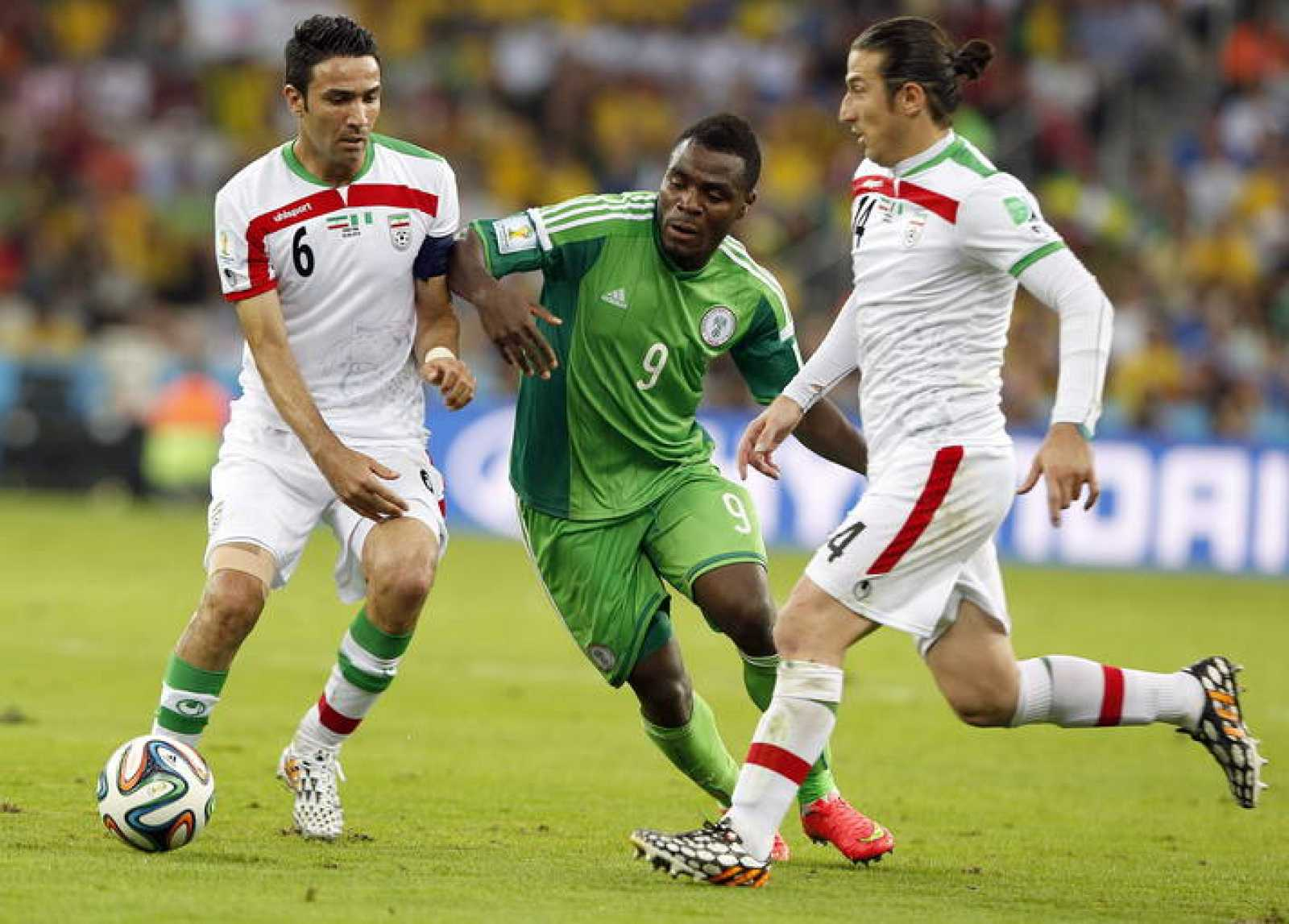El nigeriano Emmanuel Emenike defendido por Javad Nekounam y Andranik Timotian durante el partido.