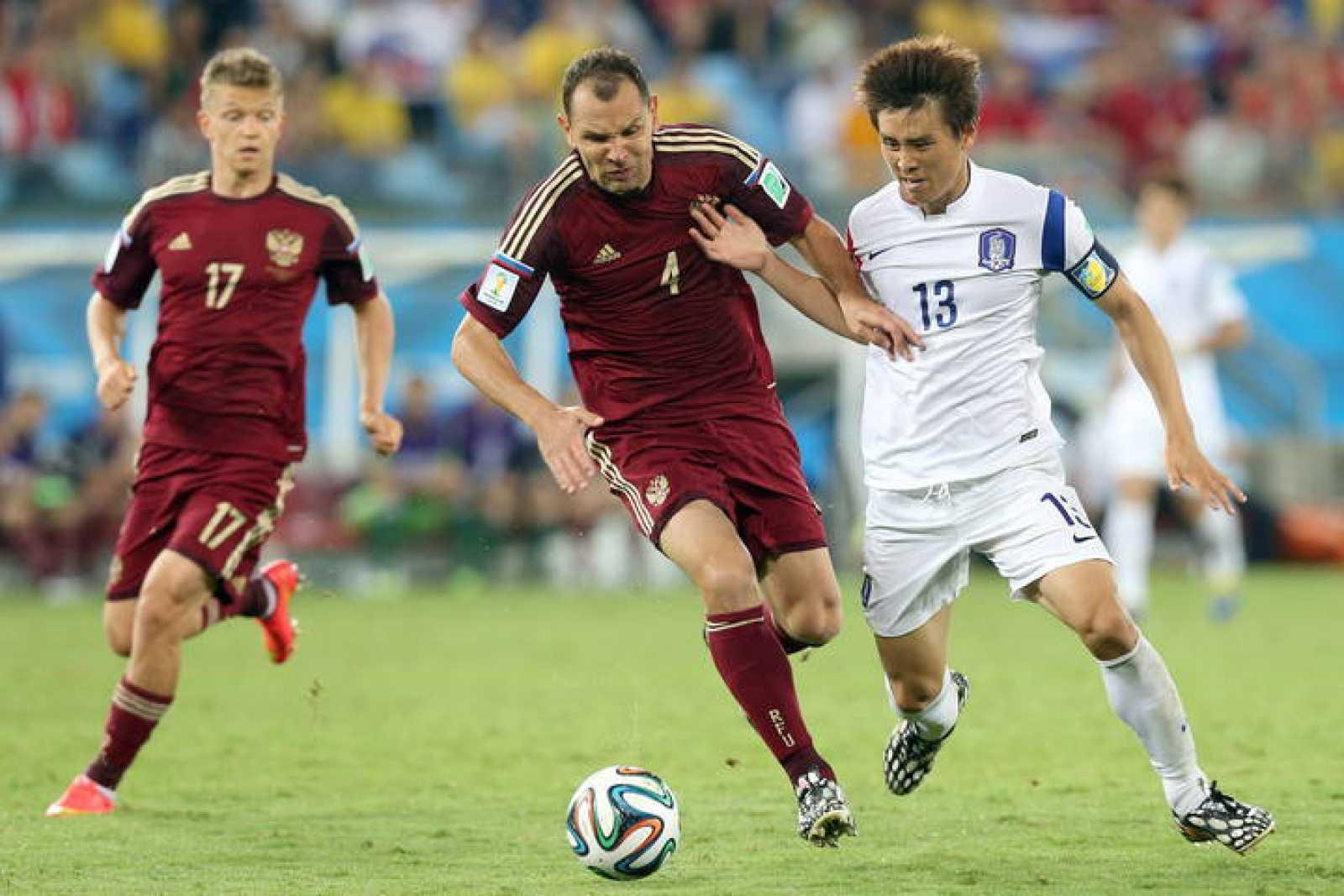 Sergei Ignashevich, jugador de la selección rusa, en una acción contra Koo Jaceol, de Coera del Sur.