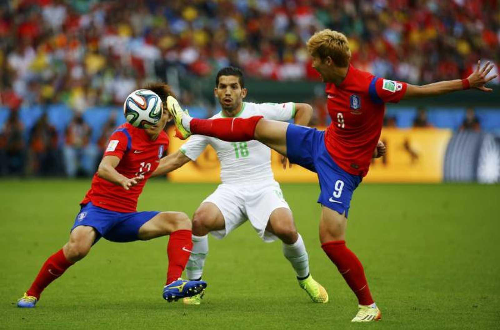 El jugador argelino Abdelmoumene Djabou (C) lucha con los coreanos Lee Yong (I) y Son Heung-min.