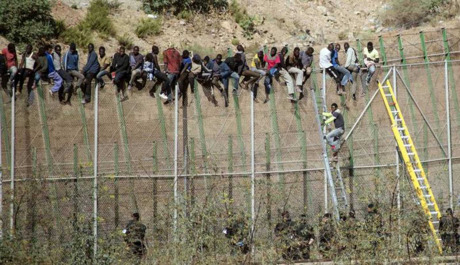 Inmigrantes subsaharianos encaramados a la valla de Melilla.