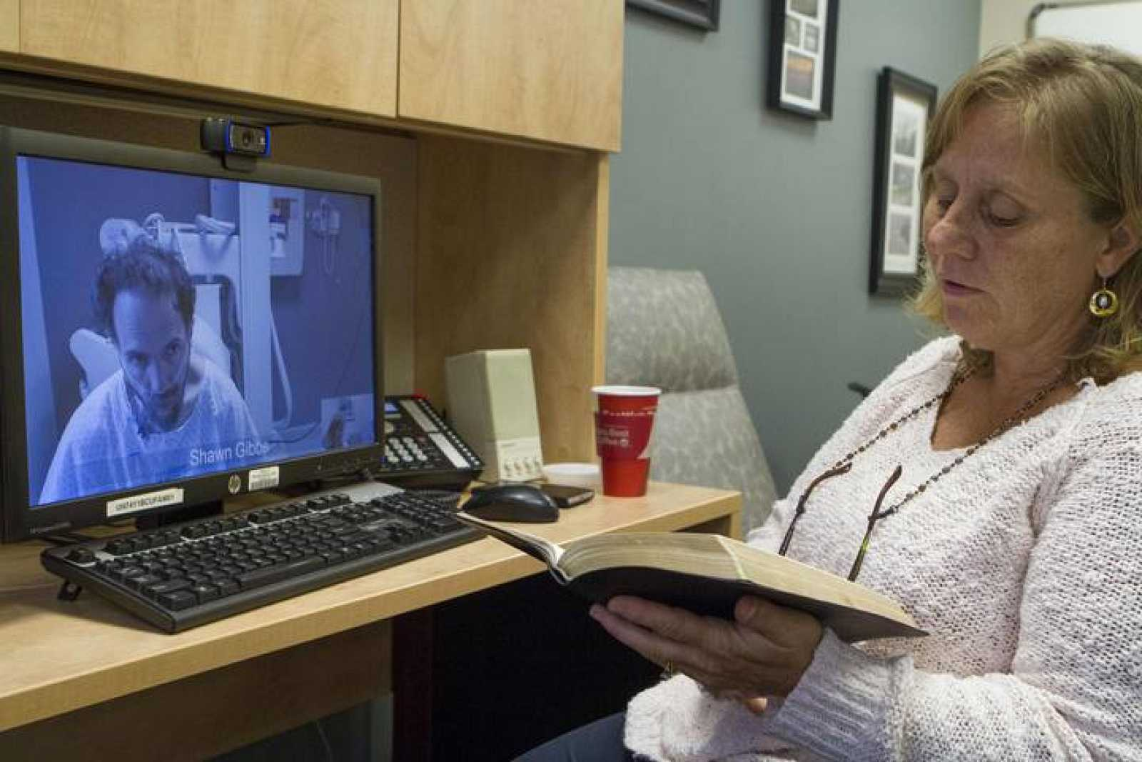 Handout shows Debbie Sacra, wife of Dr. Rick Sacra, reading Bible verses to him during a video conference at the Nebraska Medical Center in Omaha, Nebraska