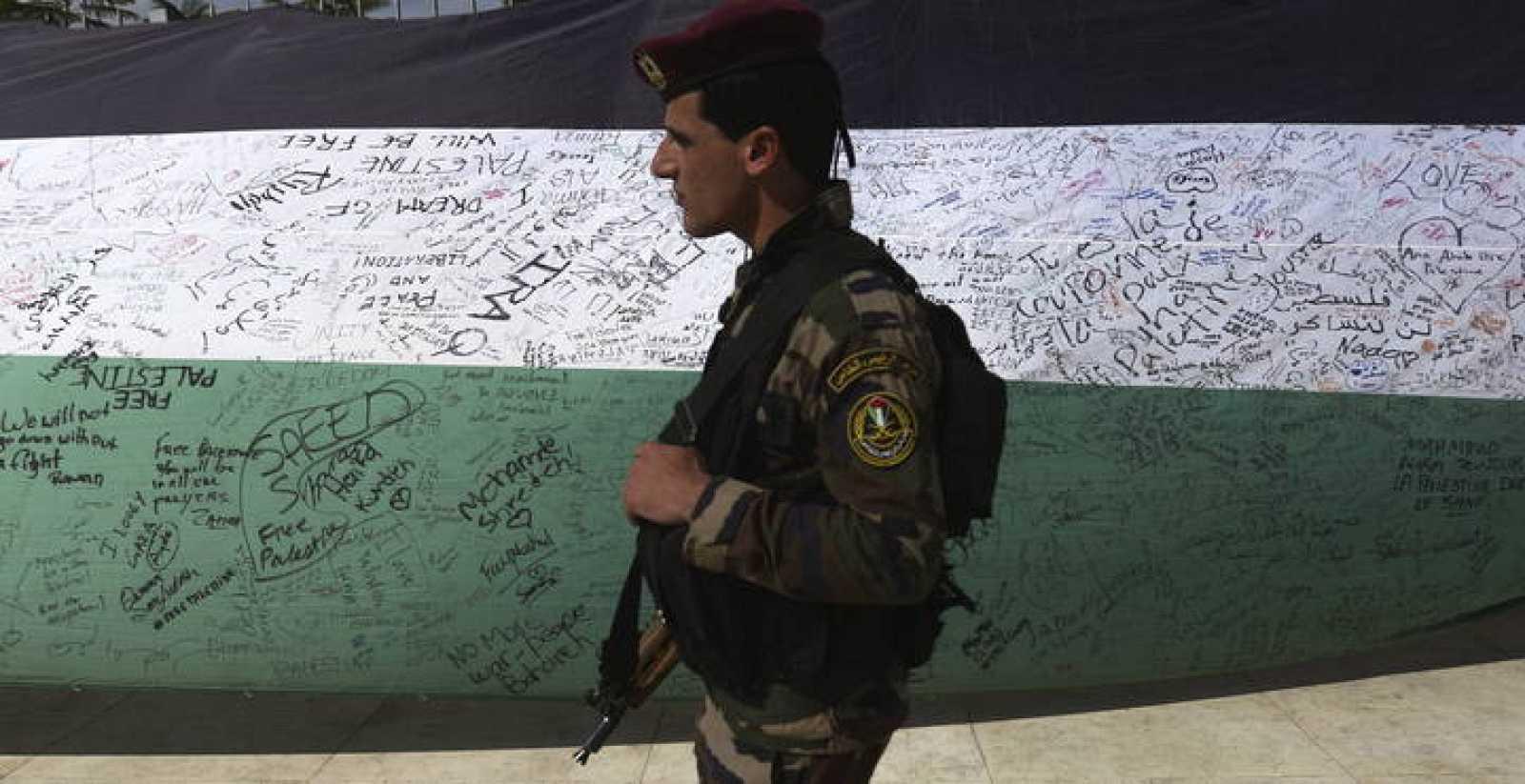 Un miembro de las Fuerzas de Seguridad palestinas pasa junto a una bandera palestina de 66 metros de largo en Ramalah
