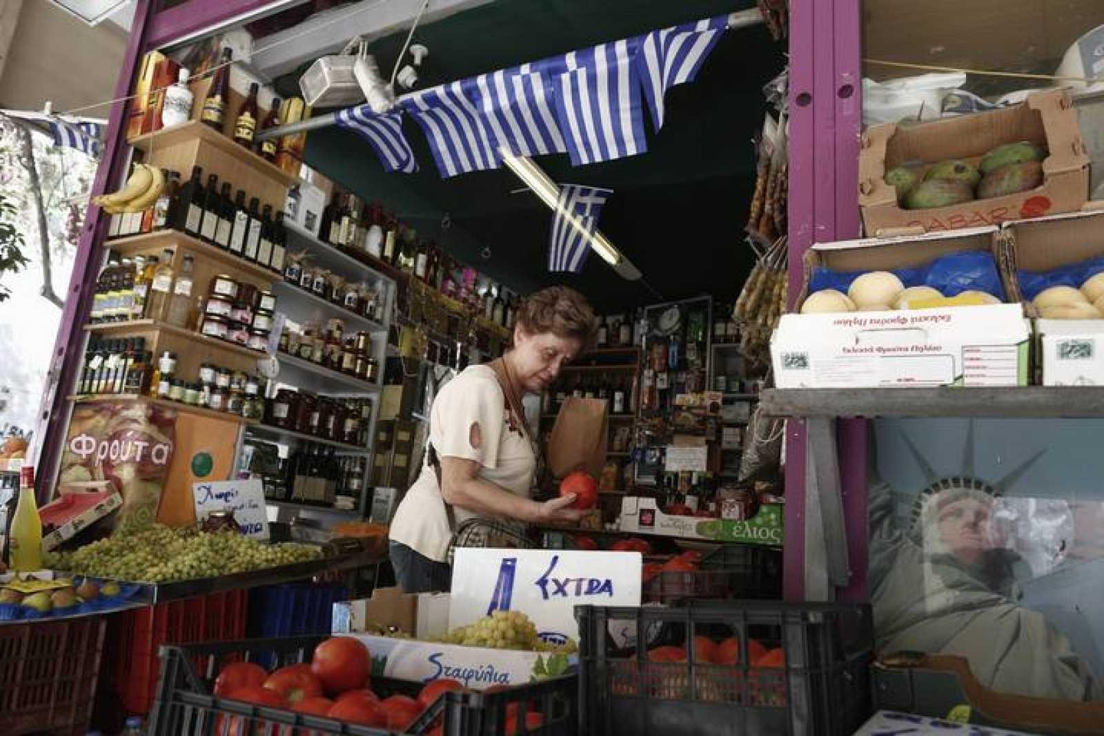 Una mujer compra tomates en una frutería en el centro de Atenas