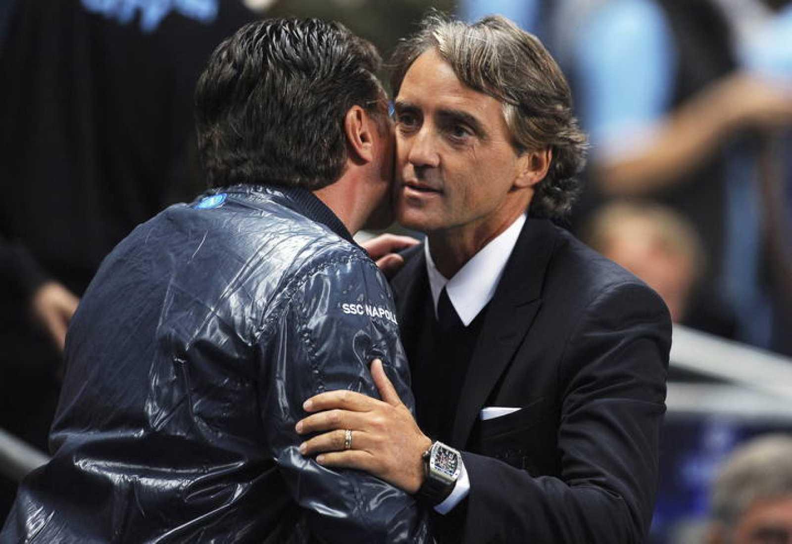 Fotografía de archivo fechada el 14 de septiembre de 2011, del entonces entrenador del Nápoles, Walter Mazzarri (i), mientras saluda al entonces técnico del Manchester City, Roberto Mancini.