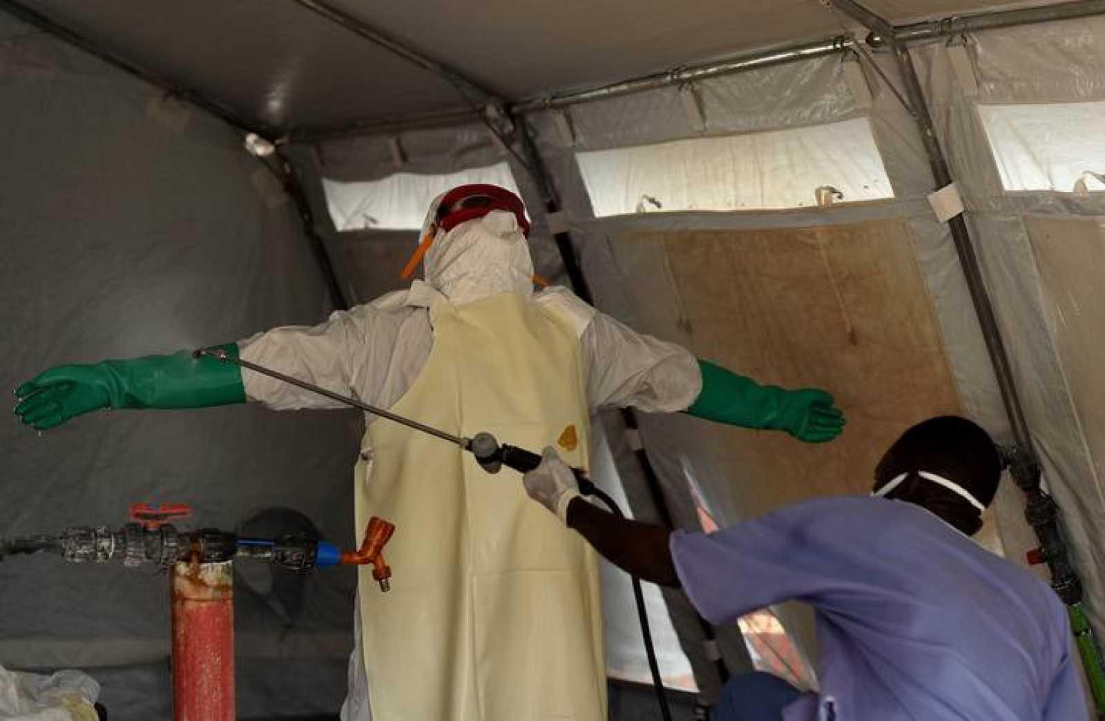 Un enfermero con un traje protector es desinfectado en Kenama, centro para el tratamiento del ébola en Sierra Leona