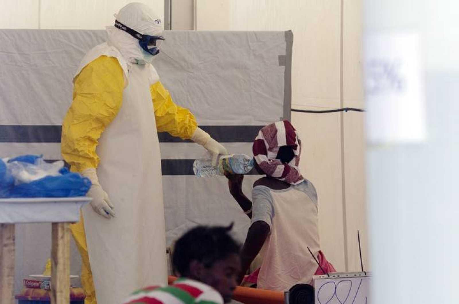 Un enfermero con traje protector atiende a enfermos de ébola en Guinea