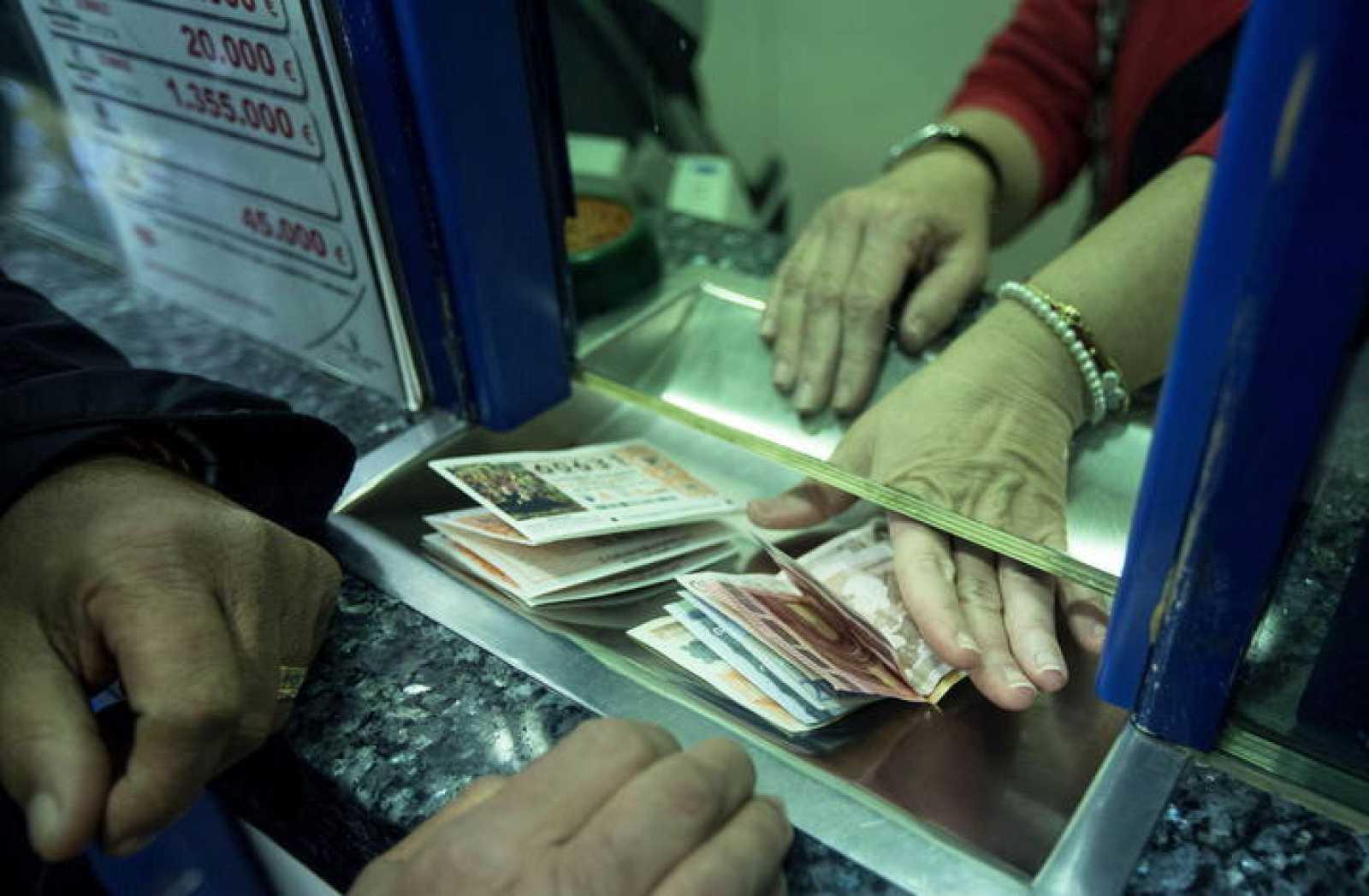 Un hombre compra varios décimos en la administración de lotería Bello, en Valencia