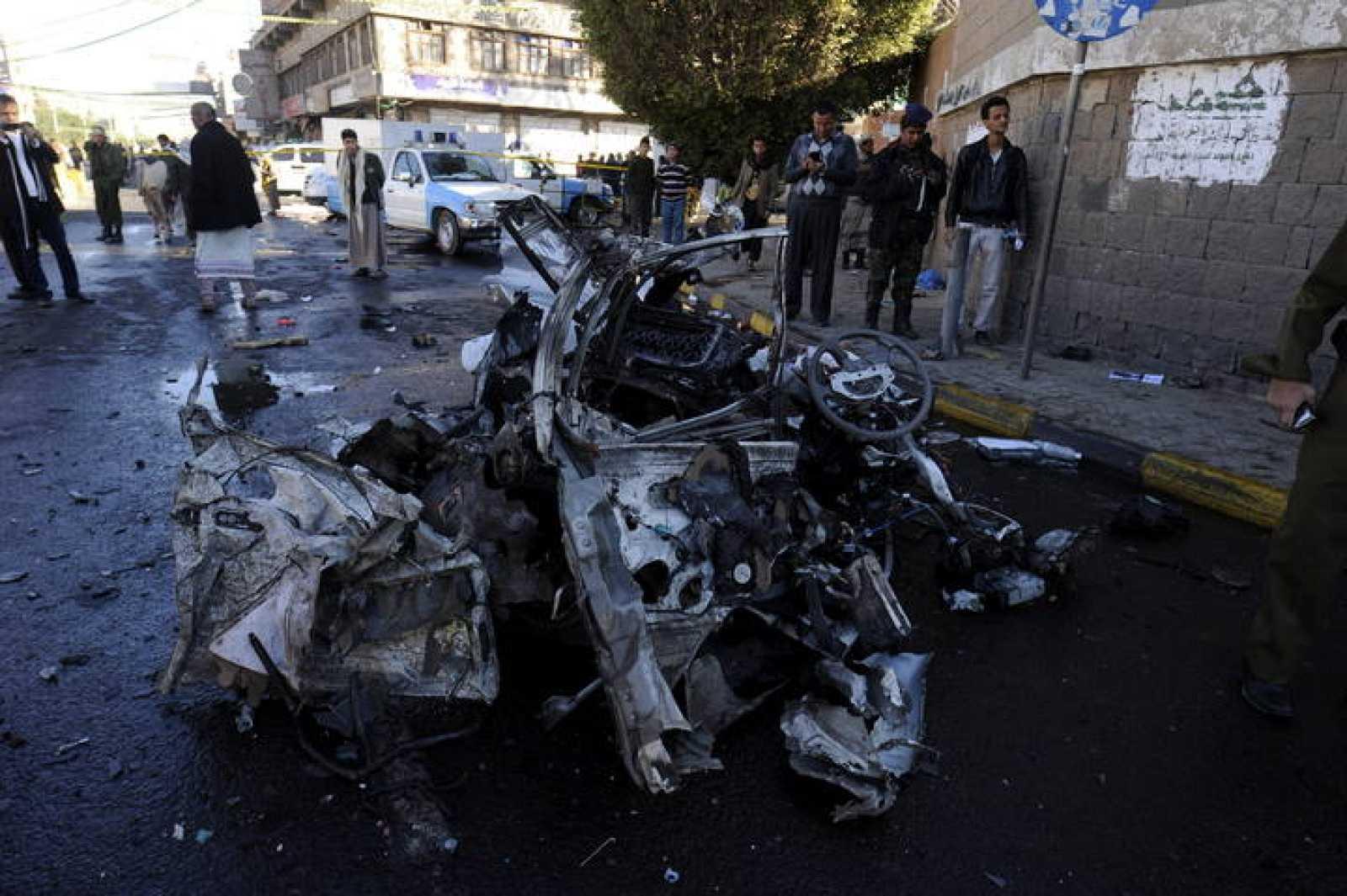 Yemeníes pasan junto a los restos del vehículo usado para un ataque suicida contra una academia de policía en Saná,