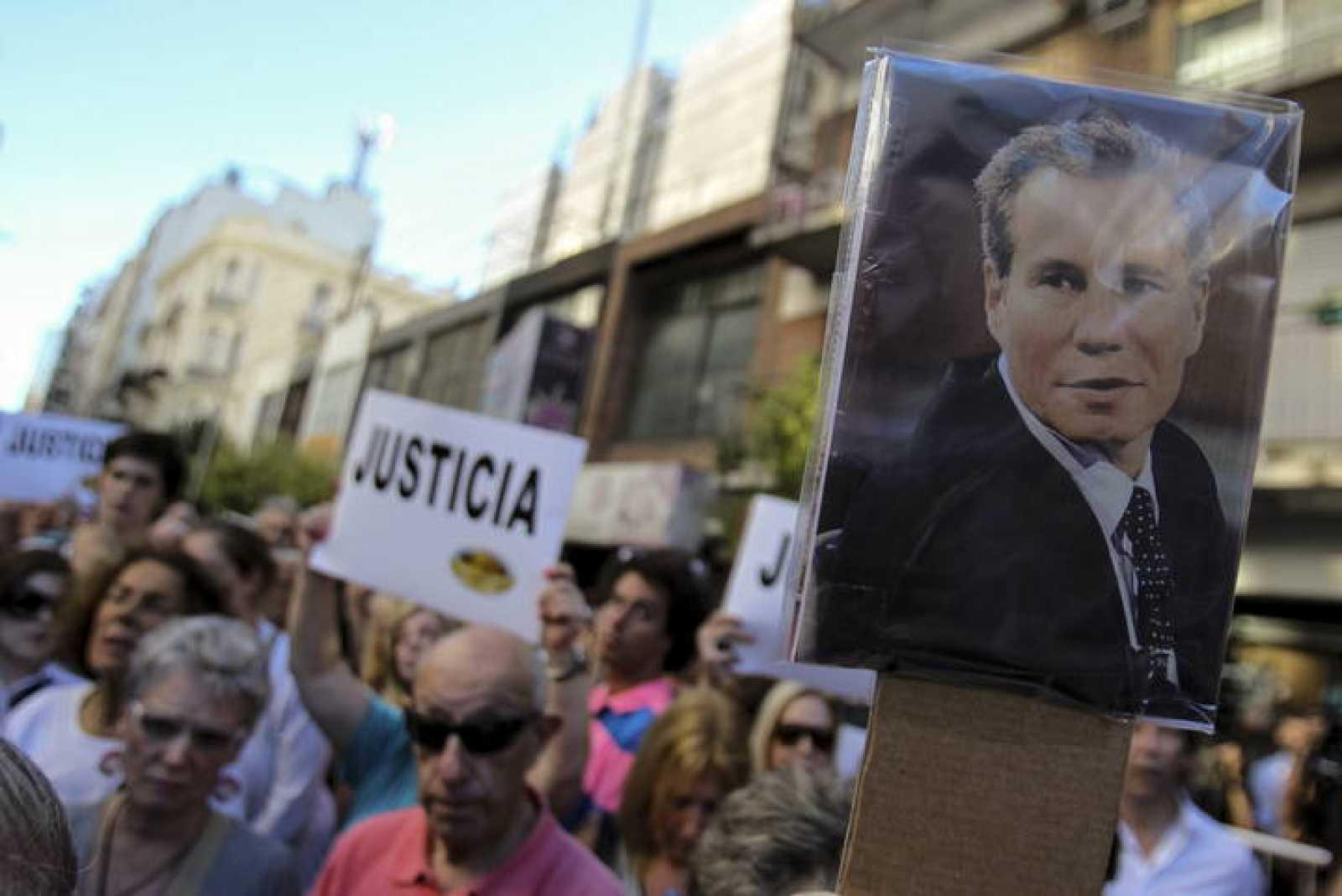 Un grupo de personas participa en una manifestación para exigir justicia tras la muerte del fiscal argentino Alberto Nisman en el exterior de la sede de la AMIA en Buenos Aires.