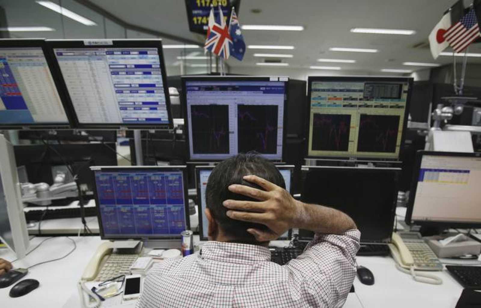 Un operador frente a los monitores del mercado de divisas de Tokio este lunes