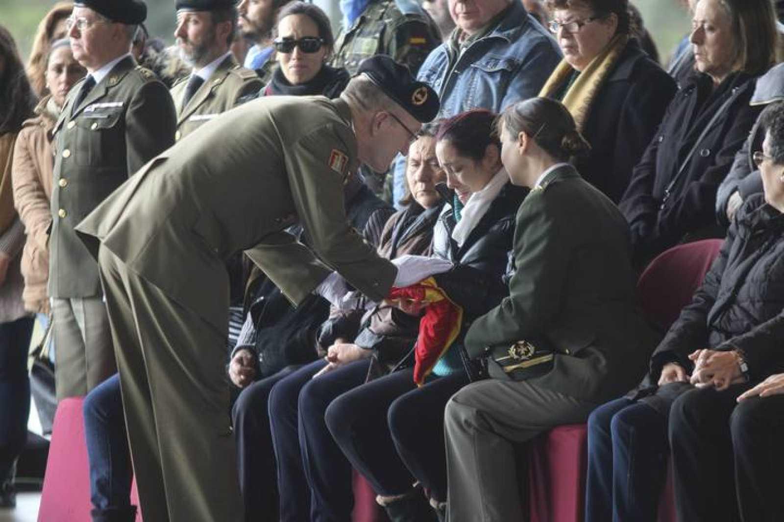 El teniente coronal Colomer entrega la bandera a la viuda del casco azul fallecido