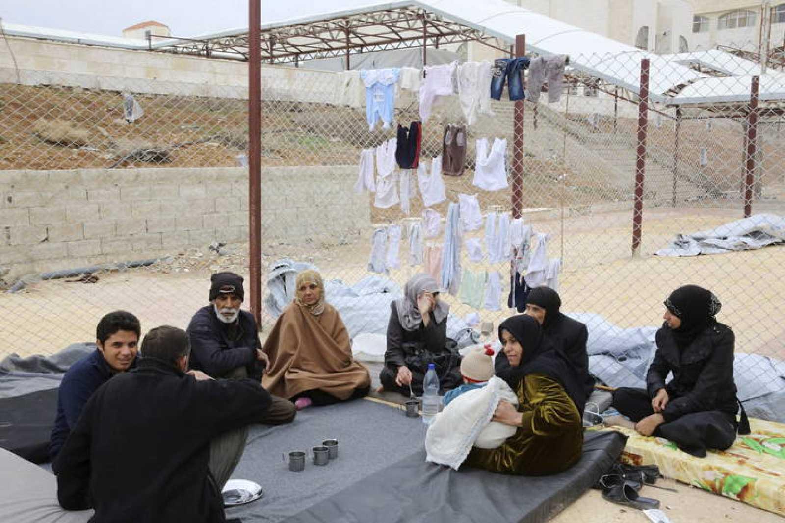 Familias evacuadas por el Ejército del área rebelde de Douma descansan en un centro de acogida temporal en una escuela en Qudsaya, a las afueras de Damasco, en Siria.