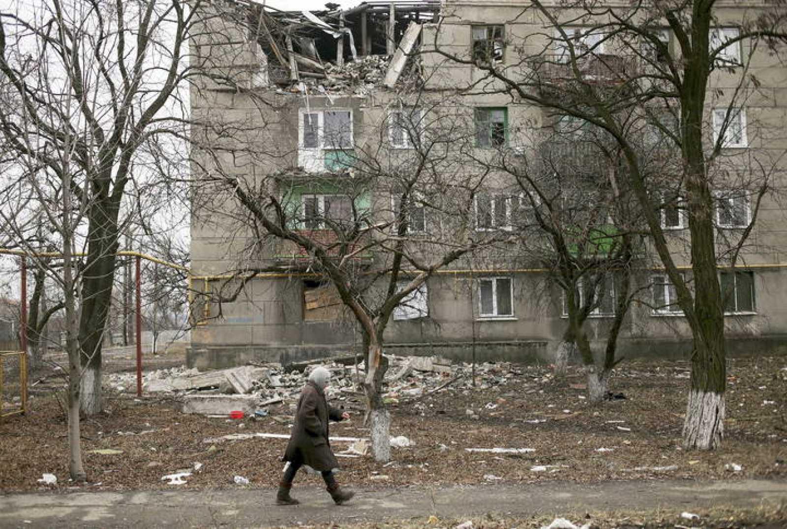 Una mujer camina por la dañada ciudad de Popasne, en el este de Ucrania