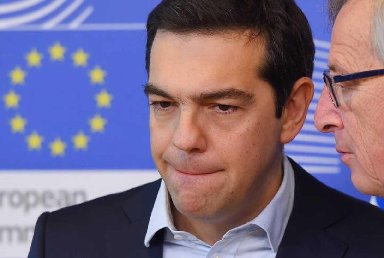 El primer ministro griego, Alexis Tsipras, escuchando al presidente de la Comisión Europea