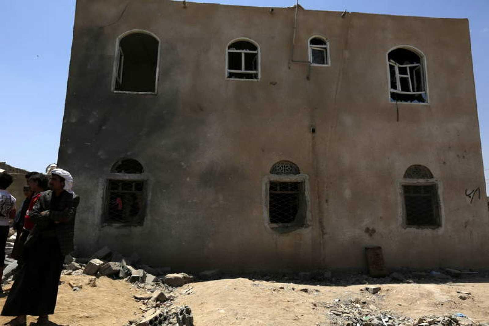 Varias personas inspeccionan sus casas destruidas en un ataque aéreo en Saná (Yemen).