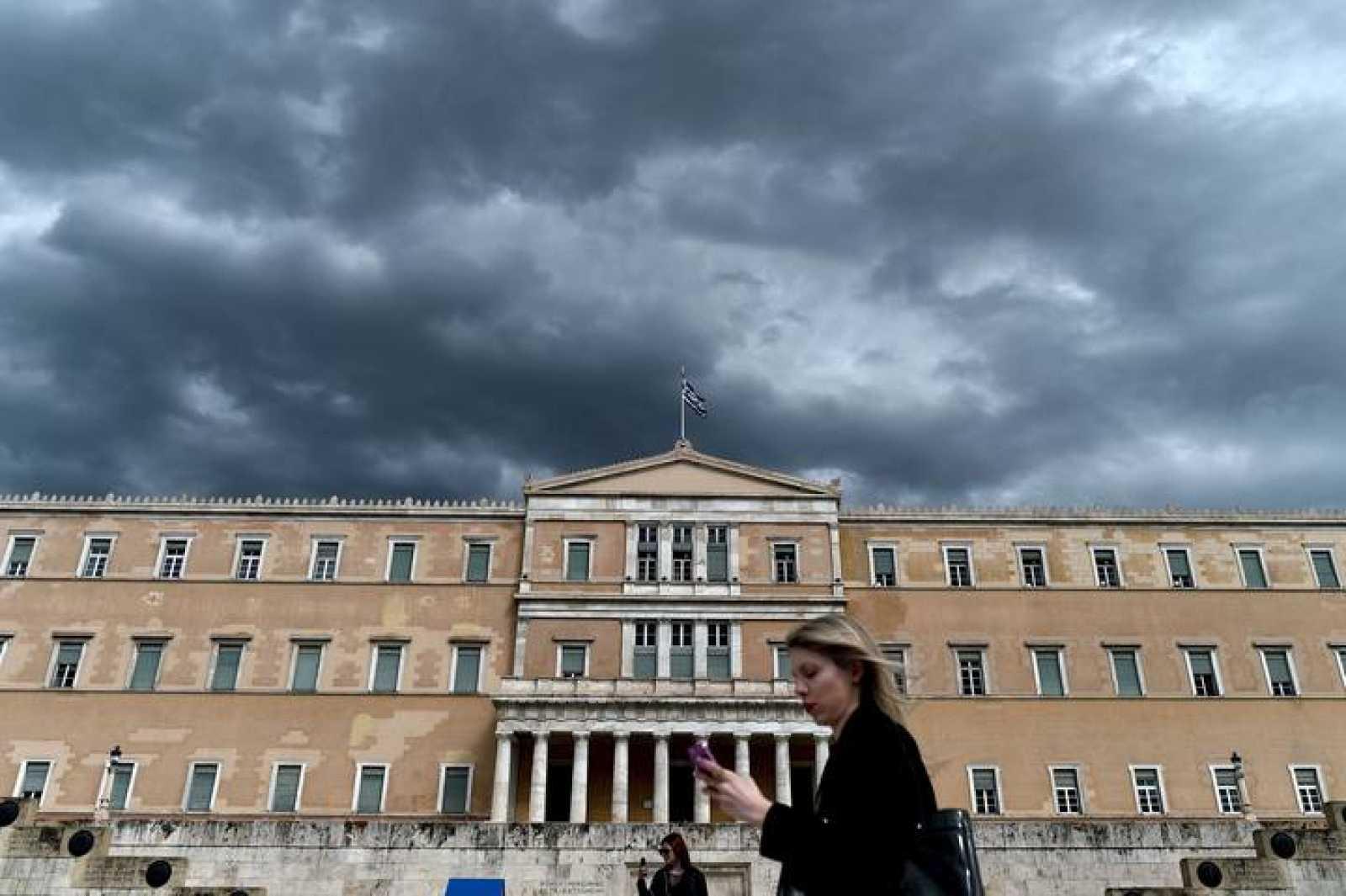 Una transeúnte pasa delante del Parlamento griego en Atenas