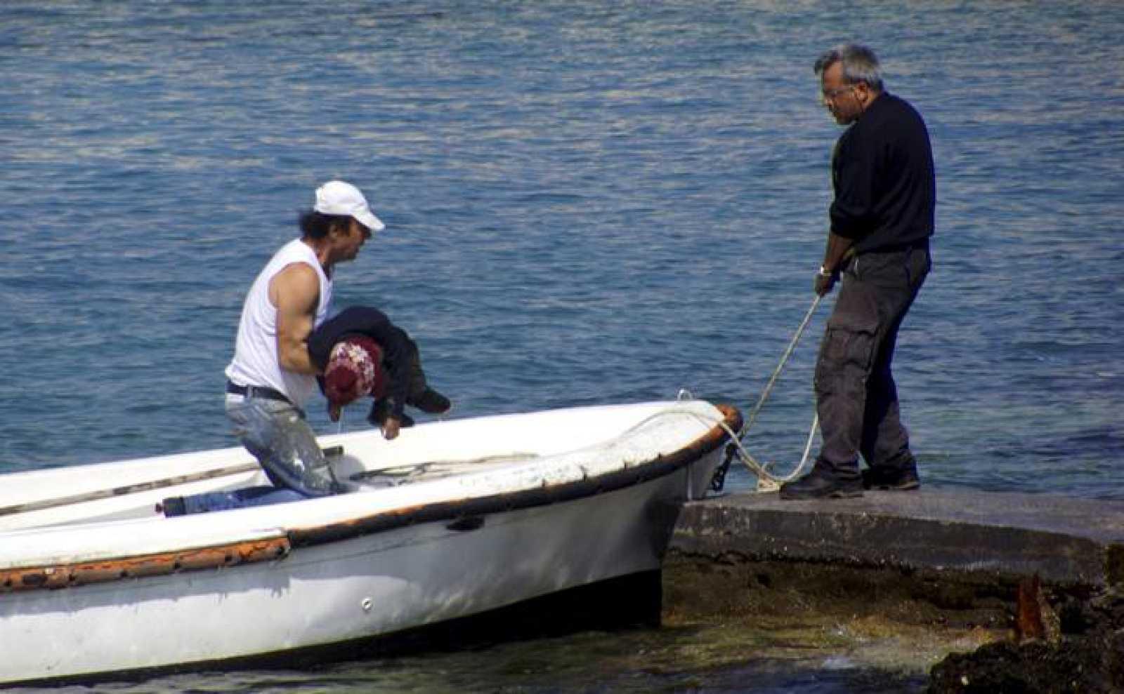 Un hombre recupera el cadáver de un niño migrante en la costa de la isla griega de Rodas.