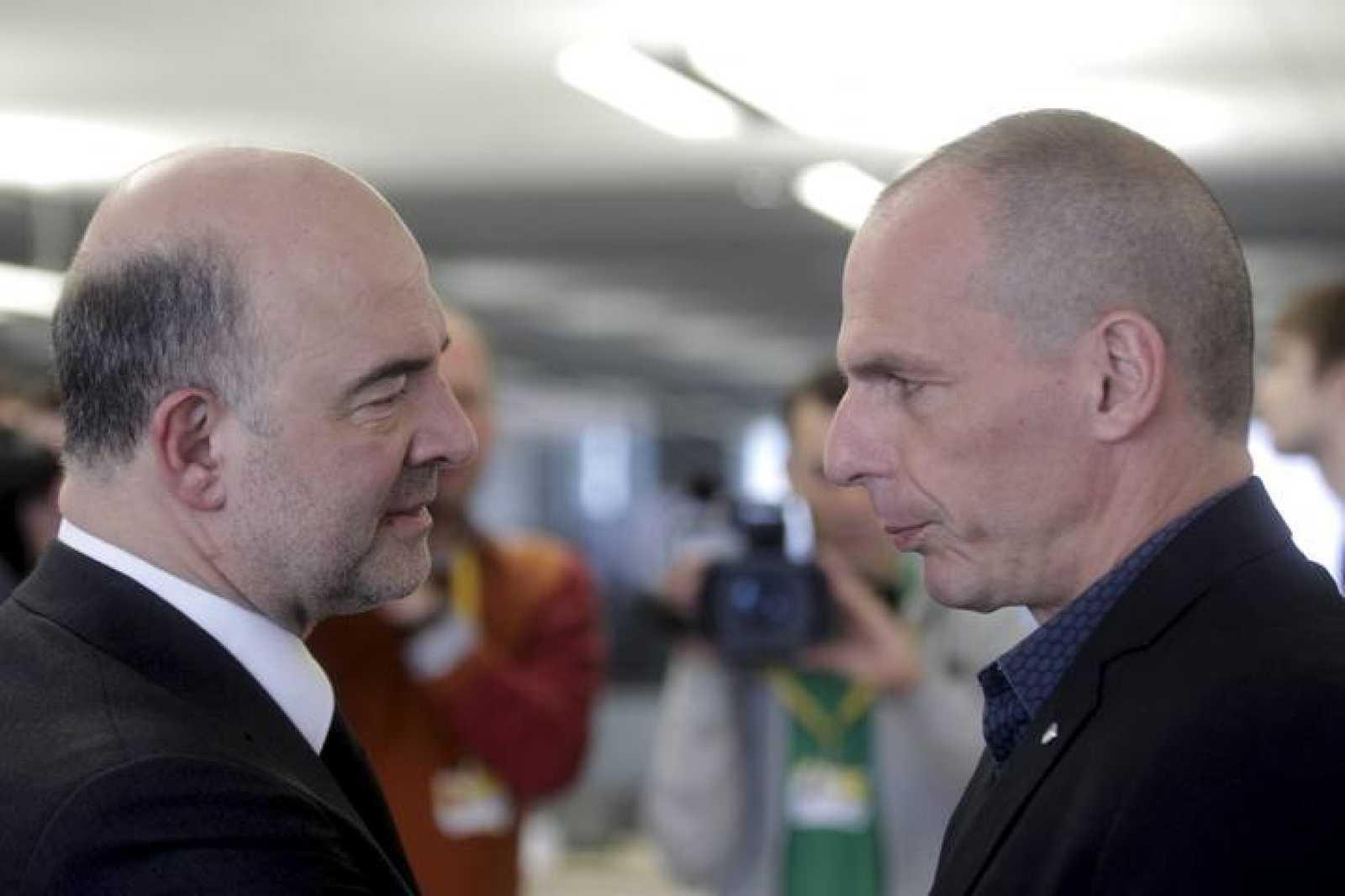 El comisario de Asuntos Económicos, Pierre Moscovici, habla con el ministro griego de Finanzas, Yanis Varufakis