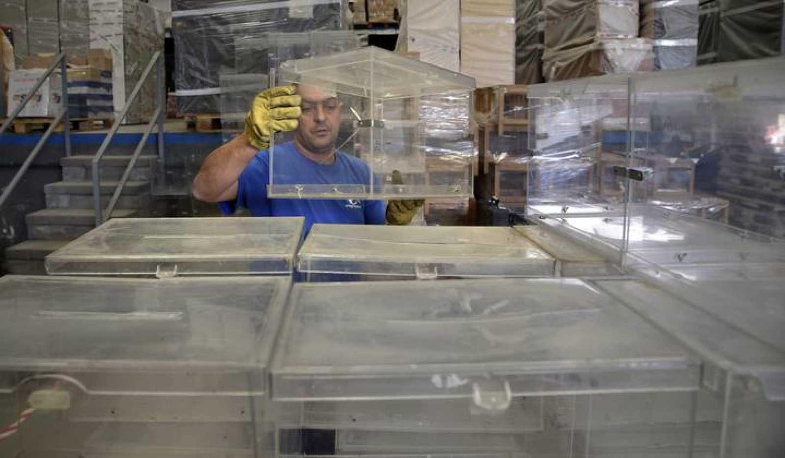 Un operario municipal apila las urnas para las elecciones del domingo en Barcelona
