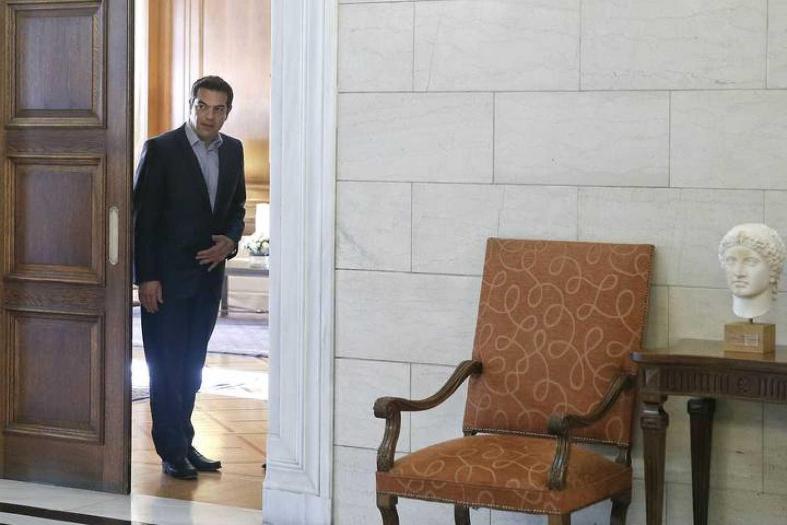 El primer ministro griego, Alexis Tsipras, se asoma a la puerta de su oficina en Atenas