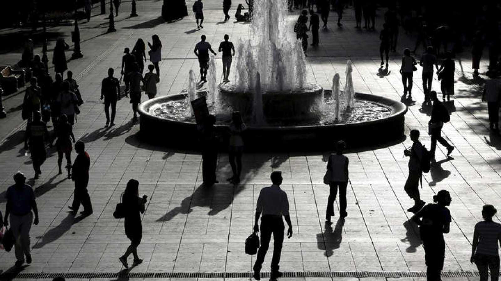 Vista de las siluetas de varias personas que pasean por la plaza Syntagma de Atenas
