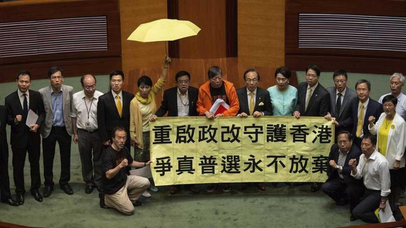 """Diputados demócratas de Hong Kong (en el centro, Lee Cheuk-yan), con una pancarta a favor del """"sufragio de democracia real"""" tras la votación en el Consejo Legislativo que ha rechazado la reforma propuesta por China"""