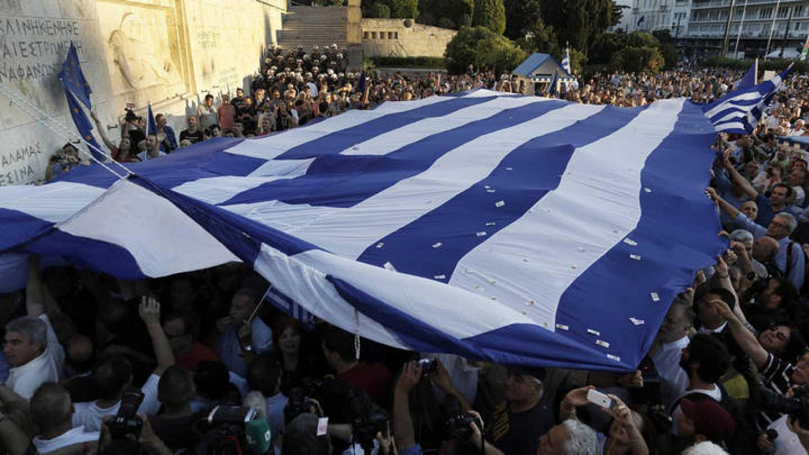 Varias personas despliegan una gran bandera griega ante Parlamento en Atenas