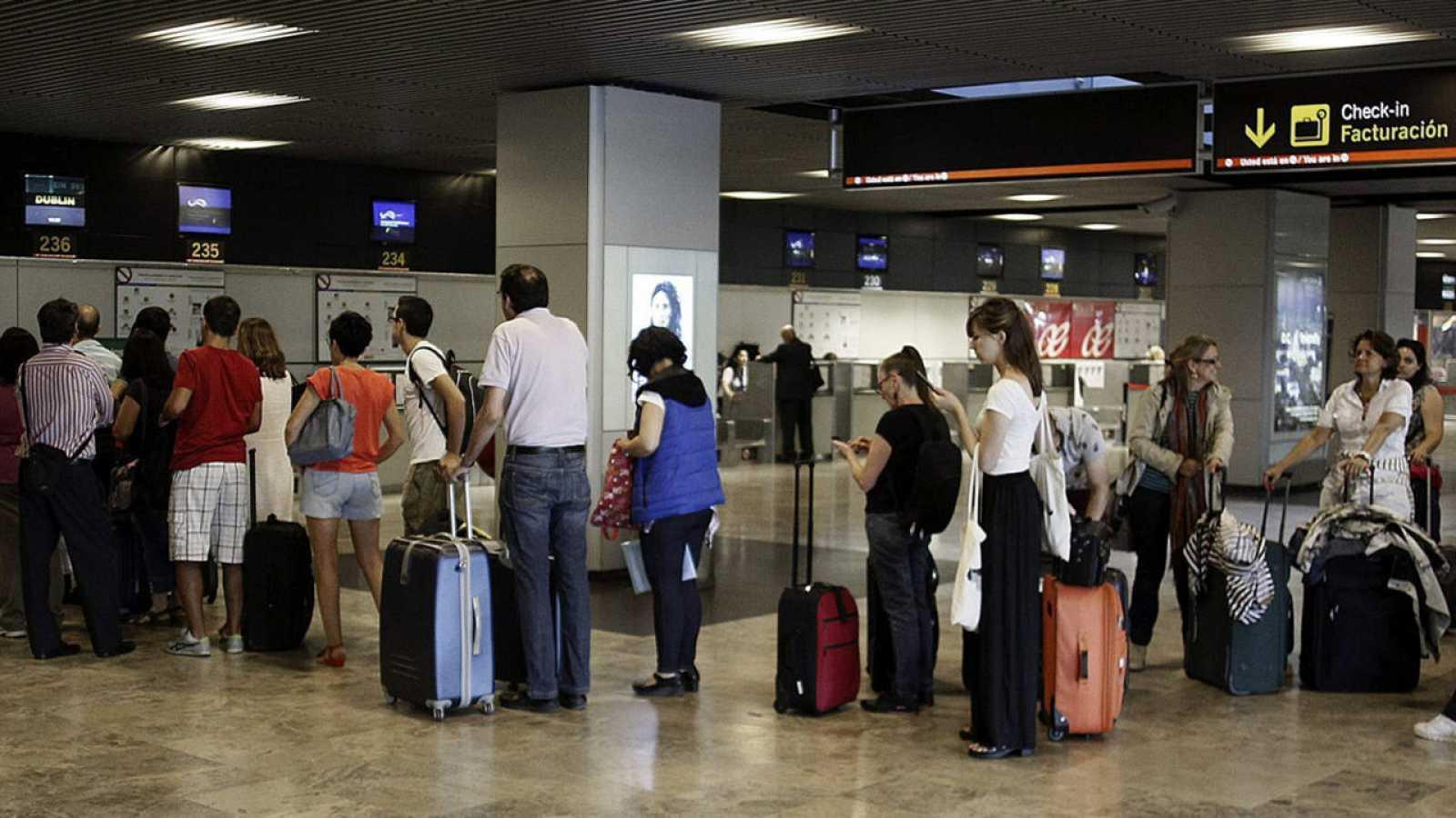 Un grupo de pasajeros hace cola ante un mostrador de facturación de Barajas