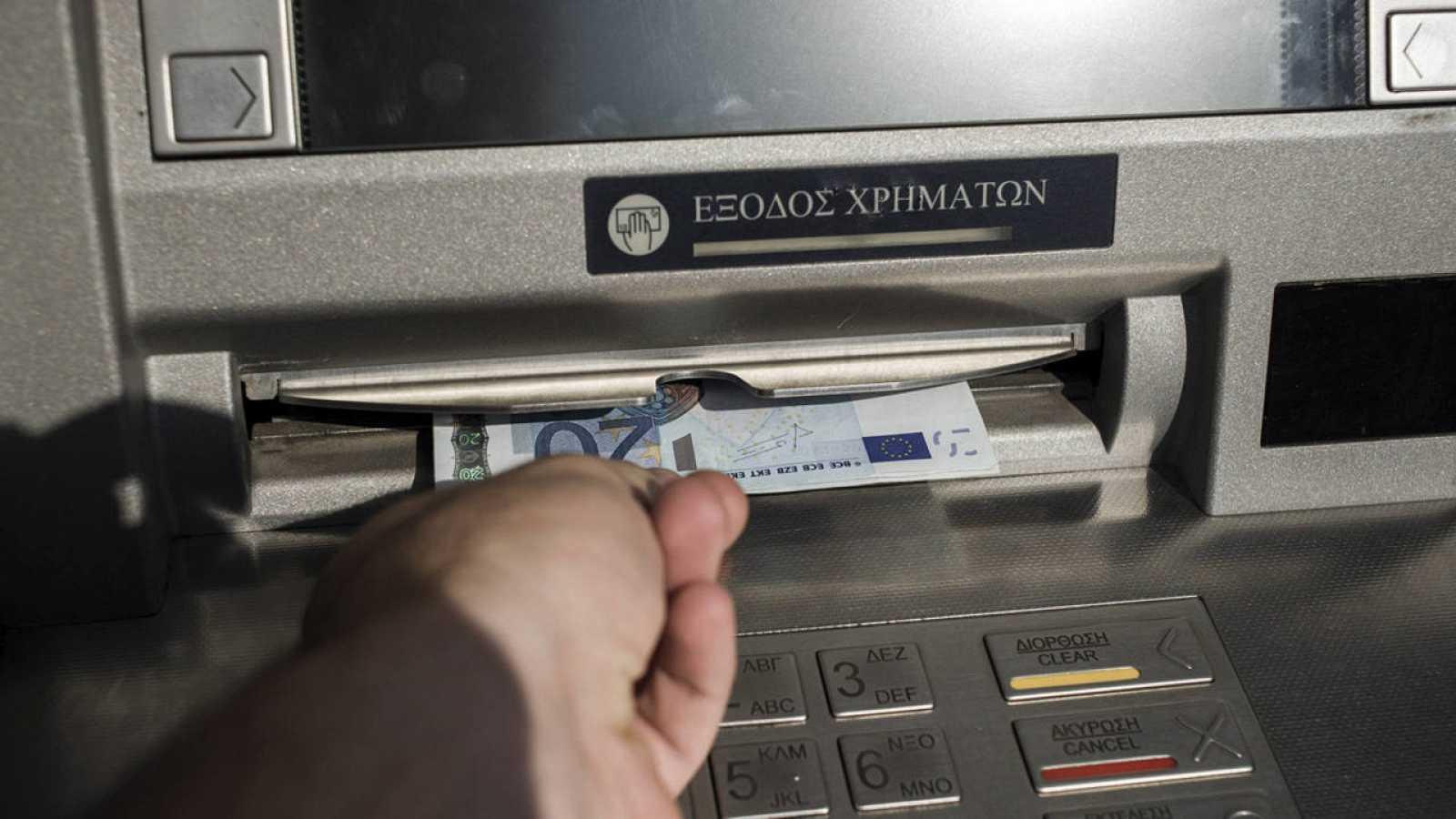 Una personas saca 60 euros de un cajero en Atenas